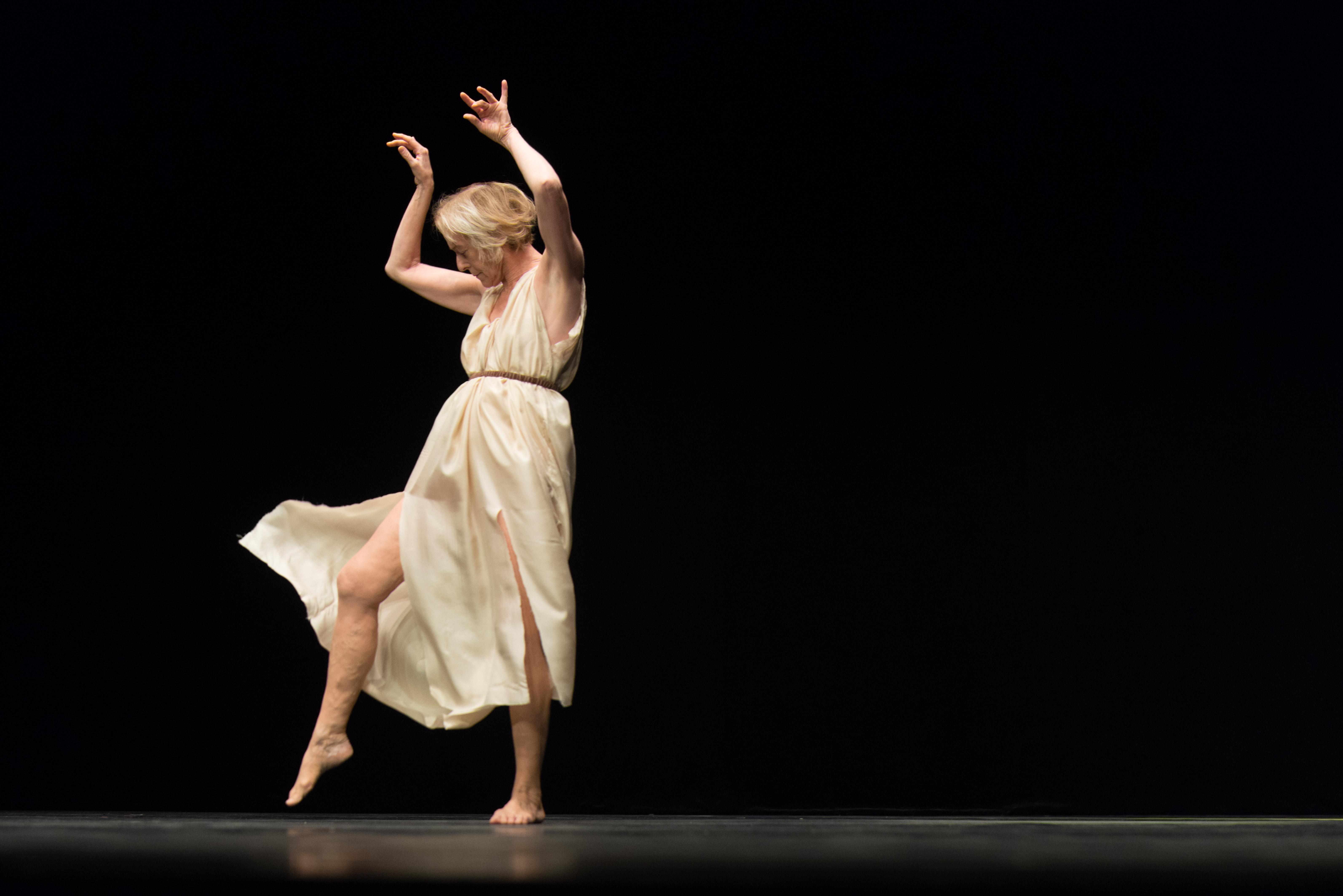 Die 70-jährige Tänzerin Elizabeth Schwartz als Isadora Duncan in graziler Pose in einem weißen klassizistischen Kleid