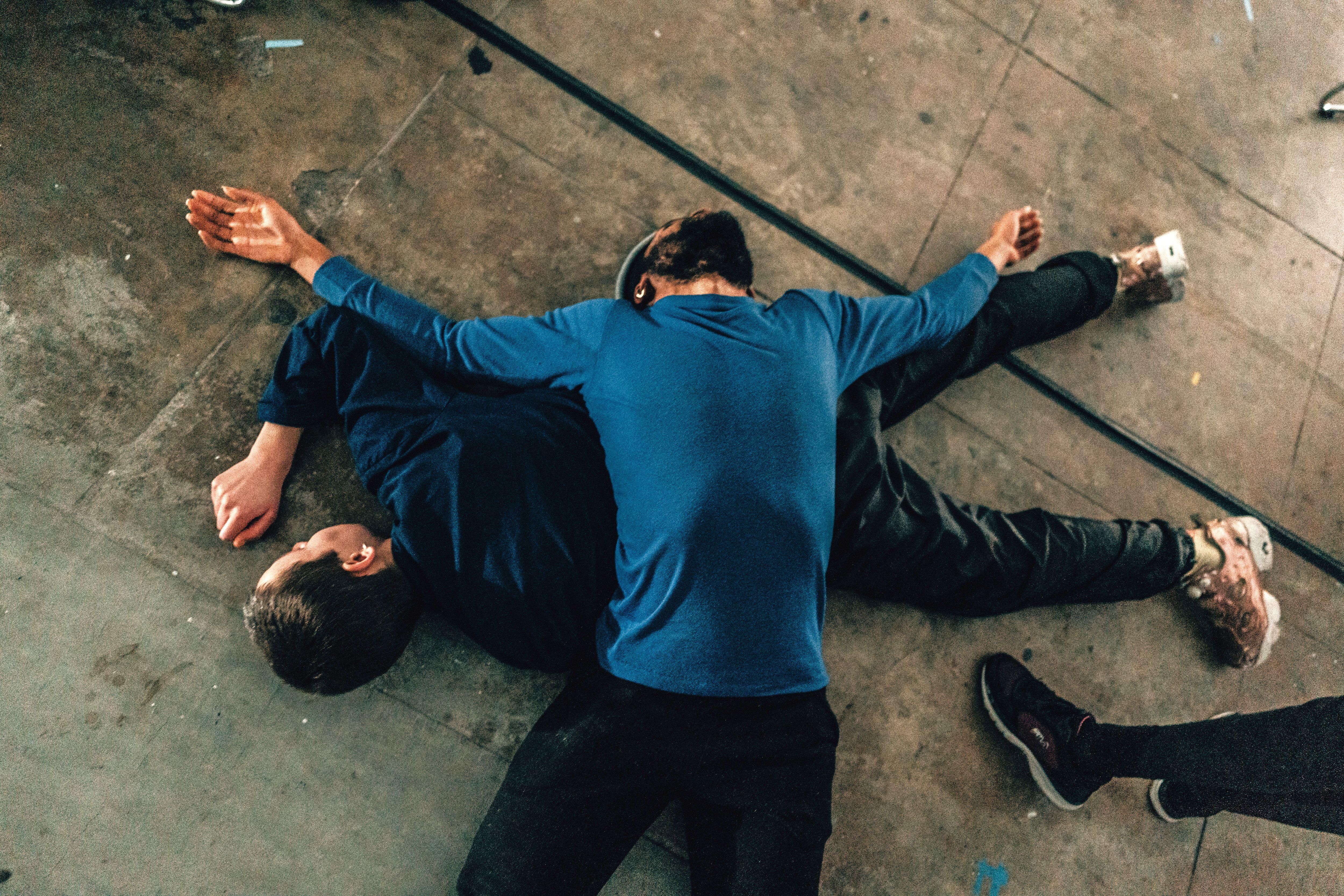 zwei Tänzer liegen aufeinander auf dem boden