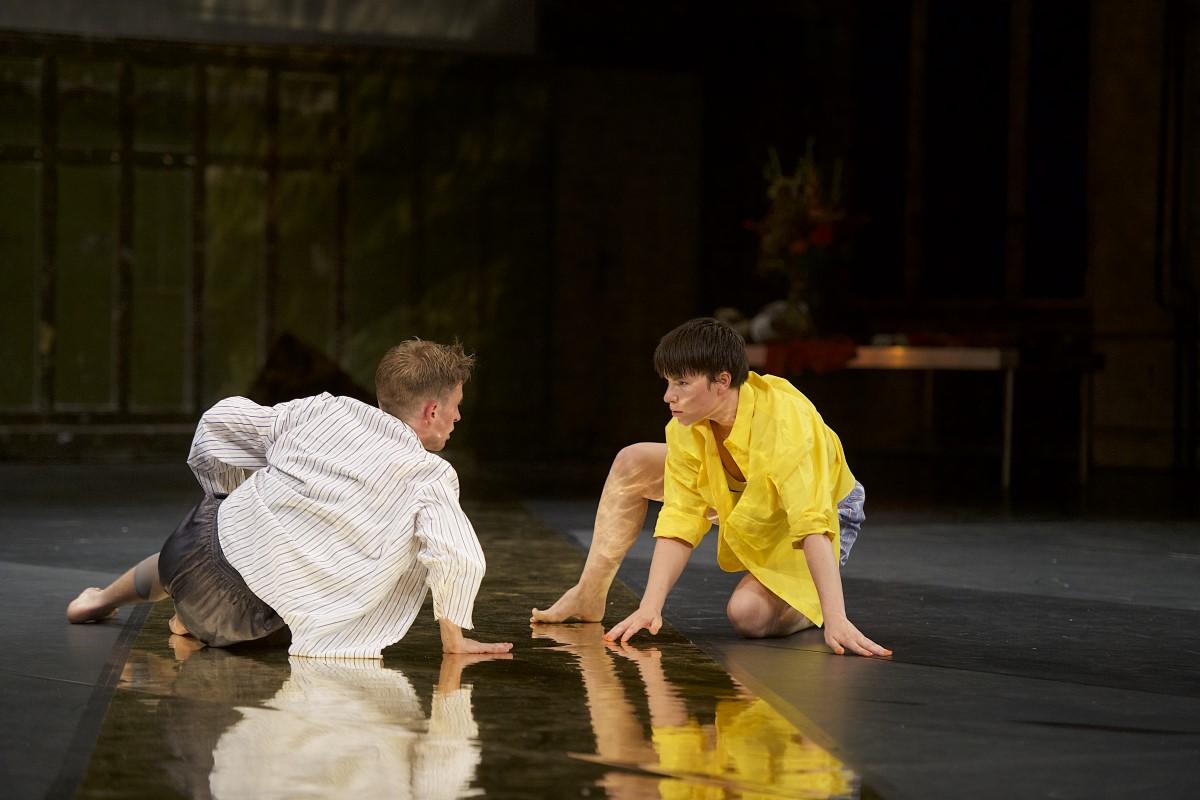 zwei Tänzer schauen einander intensiv in die Augen, ihre Haltung ist halbsitzend, halbliegend