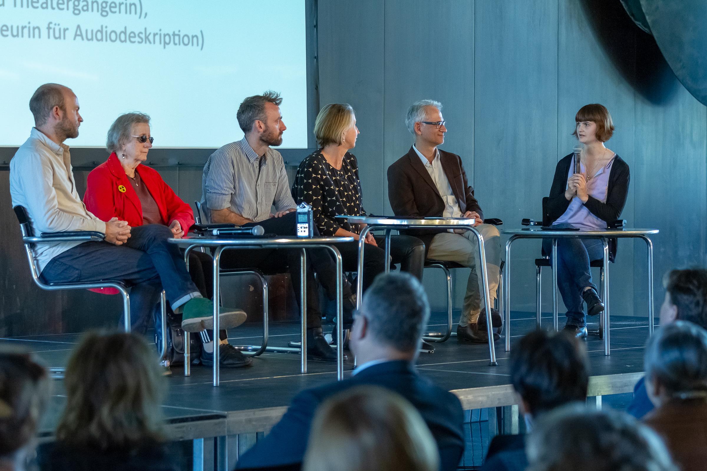 Gäste der Podiumsdisussion im Gespräch, Lavinia Knop-Waling sitzt rechts auf der Bühne und spricht in ein Mikrophon
