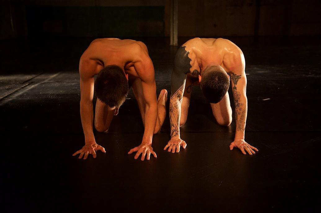 Zwei nackte Männer knien vor einem dunklen Hintergrund