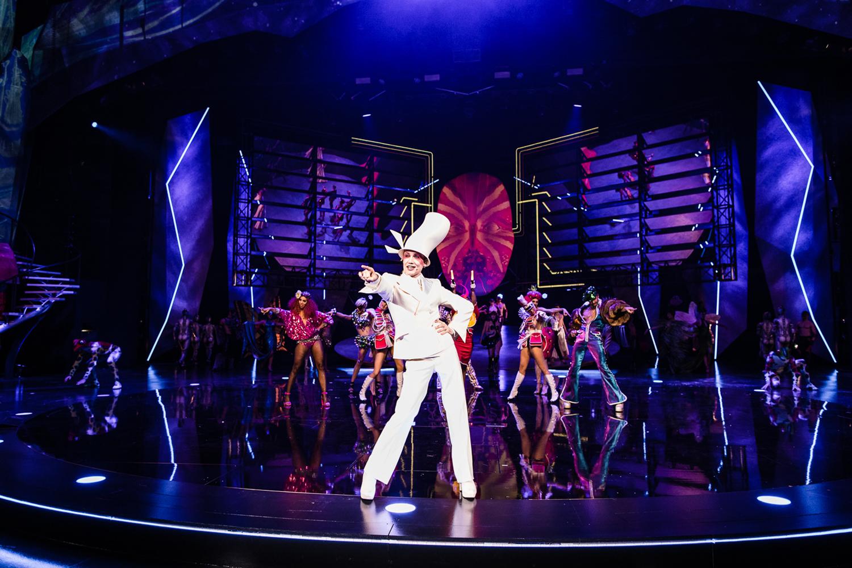 Auf einer blau eingeleuchteten runden Bühne steht ein Mann in einem weißen Anzug, breitbeinig, mit abgespreiztem Ellenbogen und der Hand auf der linken Hüfte. Mit dem rechten Arm zeigt er auf das Publikum. Weit hinter ihm stehen Tänzerinnen, die ebenfalls mit dem rechten Arm aufs Publikum zeigen. Sie tragen kurze Kostüme in leuchtend pink und schwarz.