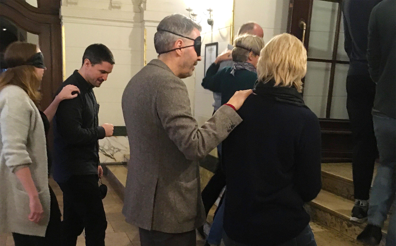 Sensibilisierungsworkshop am Berliner Ensemble. Vier Personen, die Augenbinden tragen und sich auf die Treppen der Eingangshalle des Berliner Ensembles führen lassen.