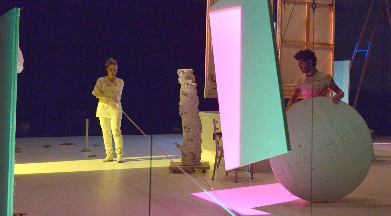 Auf einer weißen Bühne mit verschiedenen weißen Requisiten sind eine Frau und ein Mann zu sehen. Die Frau zieht an einem Seil und der Mann hält eine große runde Scheibe in der Hand. Die Bühne wird mit bunten Strahlern beleuchtet, sodass sich grüne, gelbe und rosa-farbene geometrische Formen bilden.