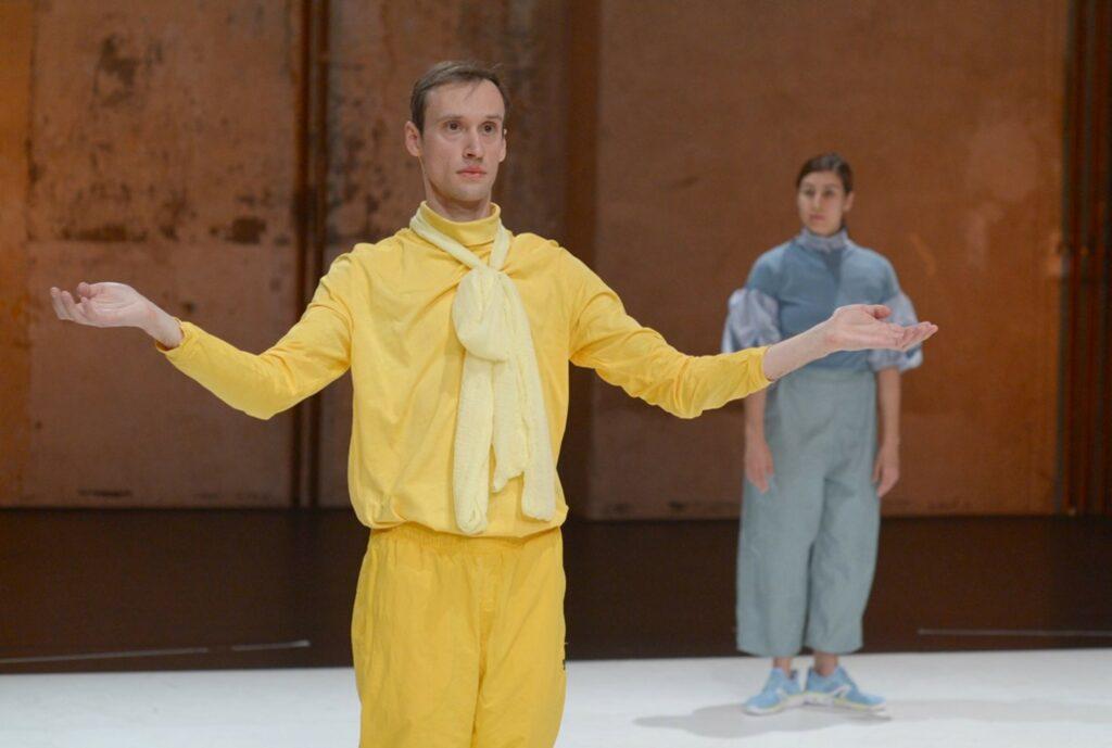 © Gerhard F. Ludwig. Ein Mann in einem Outfit aus changierenden Gelbtönen steht mit angewinkelten, seitlich ausgebreiteten Armen frontal vor der Bühne. Seine Hände   weisen nach obem. Eine Frau in hellblauer Bühnenkleidung, die schräg hinter ihm steht, schaut ihn an.