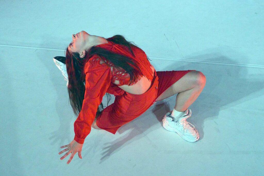 © Gerhard F. Ludwig. Eine Frau mit langen schwarzen Haaren, einer bauchfreien, langärmeligen, roten Bluse und einem roten Rock ist von schräg oberhalb der Bühne zu   sehen. Sie macht einen tiefen Ausfallschritt mit dem linken Bein. Das andere Bein ist angewinkelt und nach hinten gezogen, sodass es eine V-Form bildet. Sie beugt   ihren Oberkörper nach hinten, wobei sie fast ihren rechten weißen Sportschuh berührt.