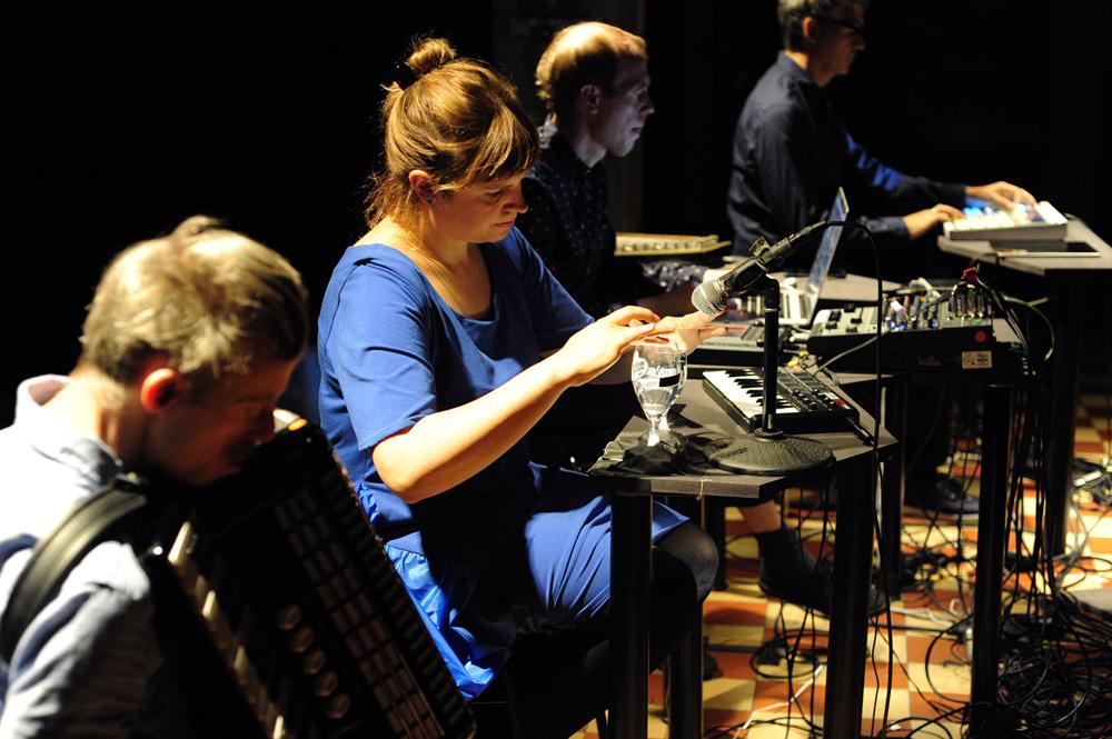 """Das Beitragsbild zeigt die Performer*innen des Kollektivs i can be your translator beim Spielen von elektronischen und analogen Musik-Instrumenten während der Performance zu """"Das Konzept bin ich"""". © Jana Mila Lippitz"""