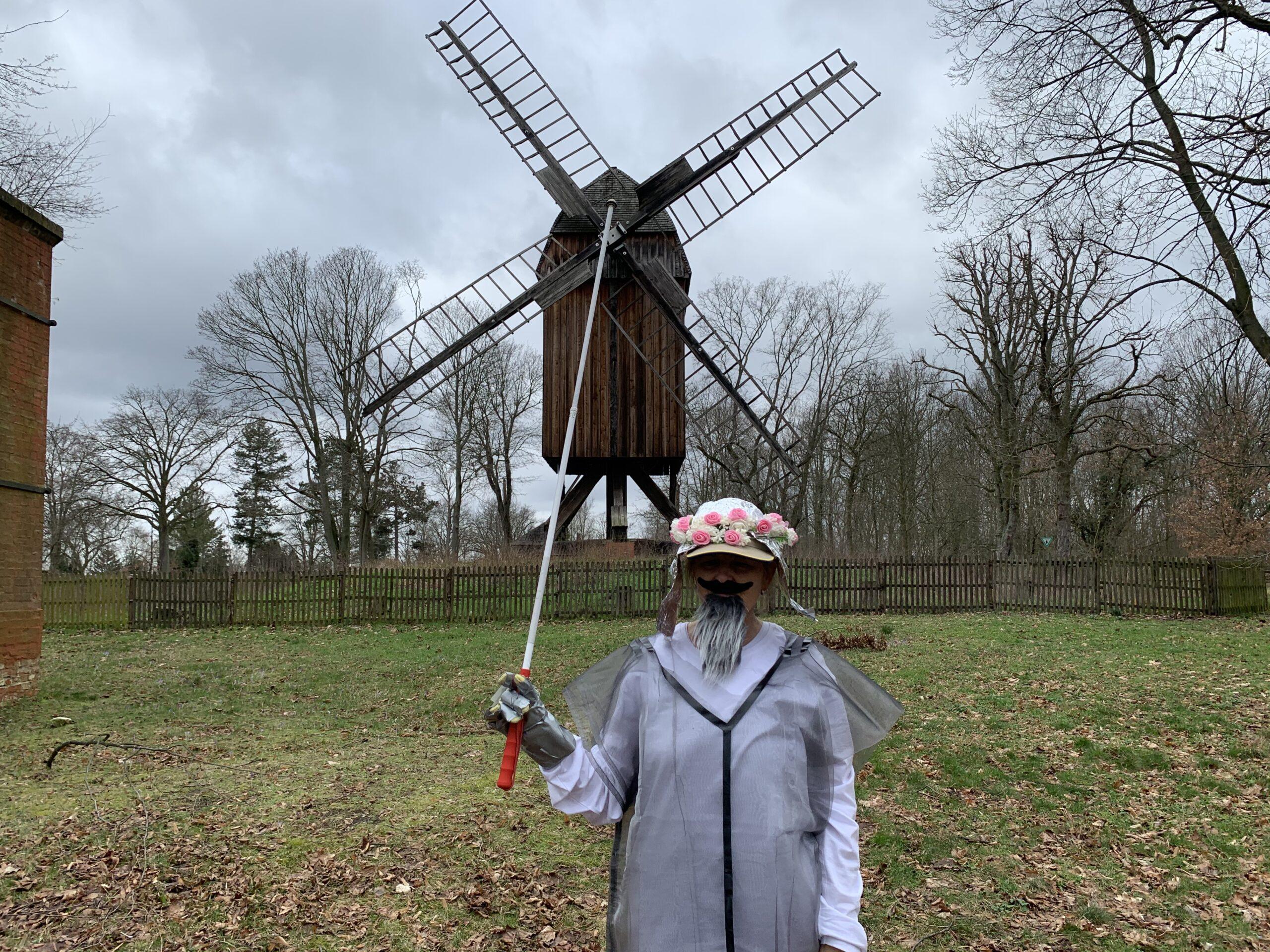 Don Quijote vor einer Windmühle. Eine Person in einem grau-durchsichtigen Regencape auf weißem Hemd mit grauem Bart und einer weißen, blumenumkränzten Mütze hält einen Stab in einem Metallhandschuh senkrecht nach oben, sodass dieser optisch die Mitte der vier Windräder von der Windmühle hinter ihr trifft.