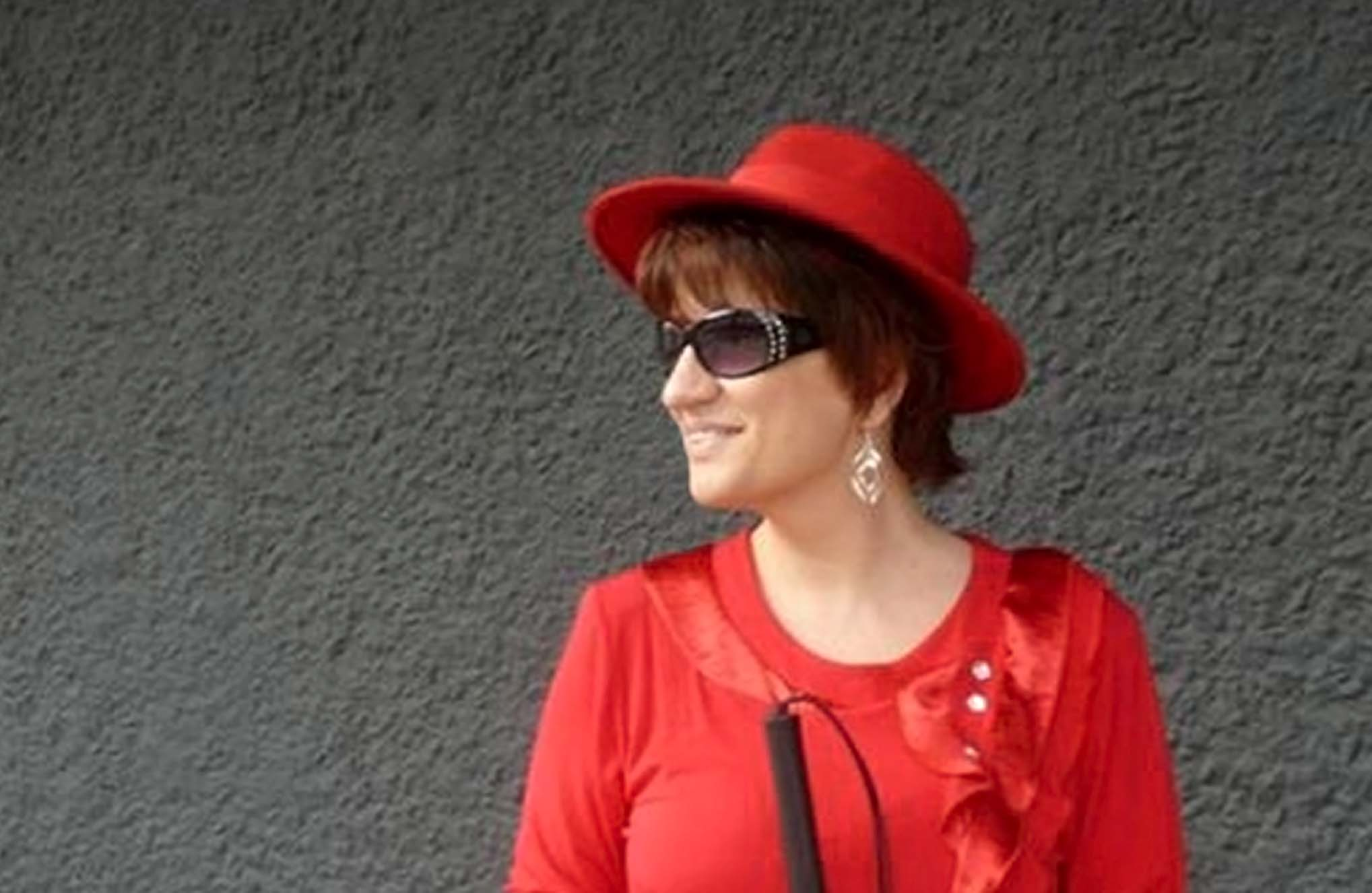 Silja Korn trägt eine rote Tunika mit Glitzer-Elementen, eine schwarze Sonnenbrille, einen Silberohrring und einen roten breitkrempigen Hut über ihren braunen mittellangen Haaren. Sie steht vor einer schwarzen Außenwand und schaut nach links.