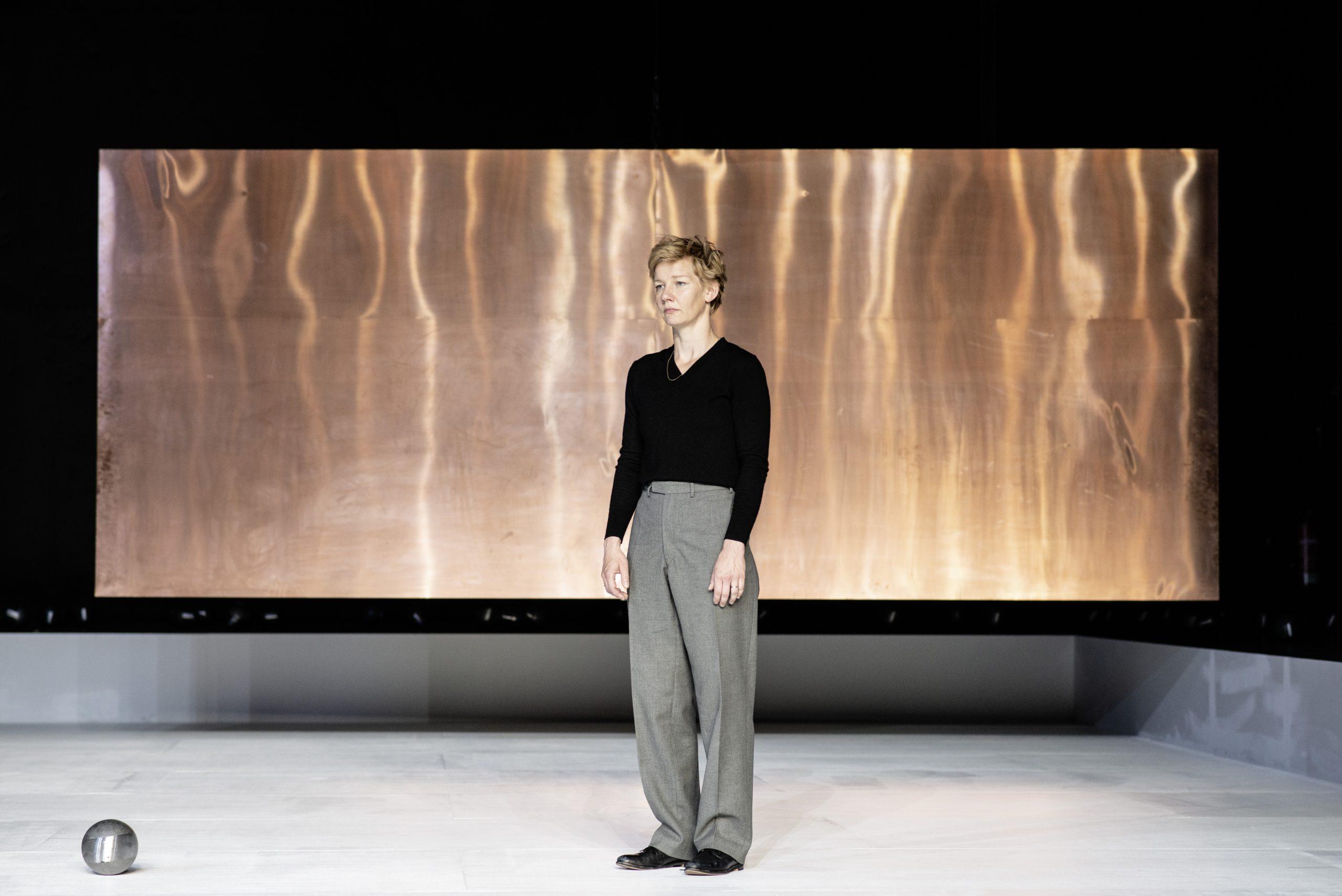 Sandra Hüller als Hamlet © JU Bochum Sandra Hüller als Hamlet steht mit hängenden Armen alleine vor einer hängenden quergelegten Kupferplatte auf einem weißen Bühnenboden. In einer Körperlänge Entfernung liegt eine grau-metallisch glänzende Kugel über die sie hinwegschaut.