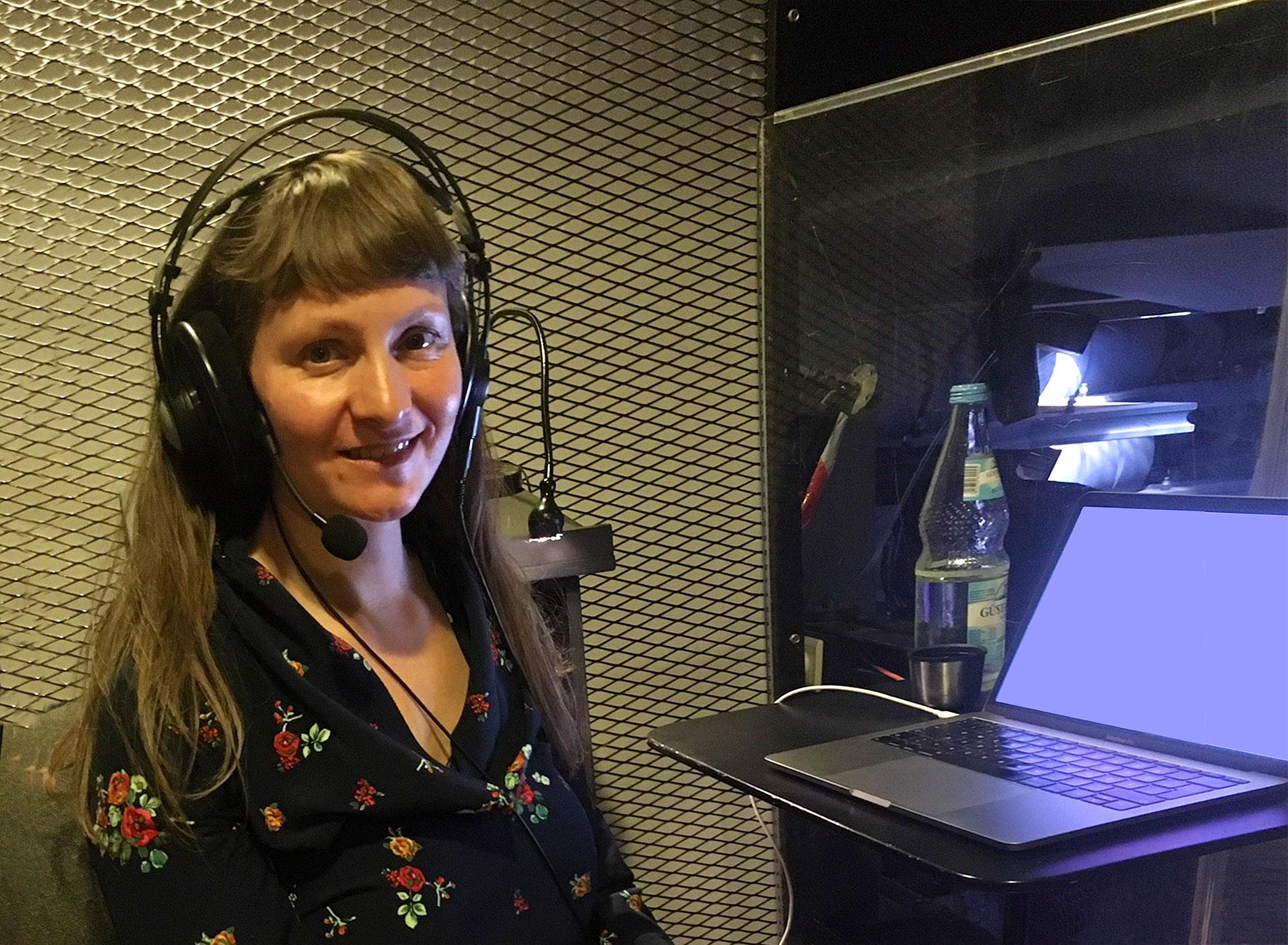 Die Audiodeskriptorin Anke Nicolai ist in der Sprecherkabine des Friedrichstadtpalastes zu sehen, im Hintergrund befindet sich ein goldglänzendes Metallgitter. Sie sitzt mit Kopfhörer und Headset vor ihrem aufgeklappten Laptop und lächelt in die Kamera. Sie trägt eine dunkelblaue Bluse mit Blütenmuster.