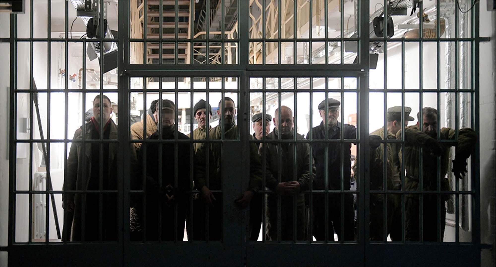 (Foto: Thomas Aurin) Hinter einem breiten vergitterten Durchgang stehen 10 Männer an der Gitterwand. Hinter ihnen ist der Gefängnistrack mit den Etagen hell erleuchtet, sodass die Männer im Dunklen stehen.