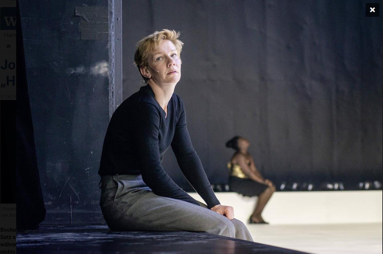 Sandra Hüller, Mercy Dorcas Otieno (v. li.) © JU Bochum. Hamlet sitzt vor einem dunklen Pfeiler auf einer langgezogenen Bank des Bühnenrandes und schaut schräg nach oben. Im hinteren Bereich der Bühne ist die sitzende Gertrud verschwommen zu sehen, die ebenfalls nach oben blickt. Die Arm- und Beinstellungen der beiden ähneln sich, sie schauen jedoch in unterschiedliche Richtungen.