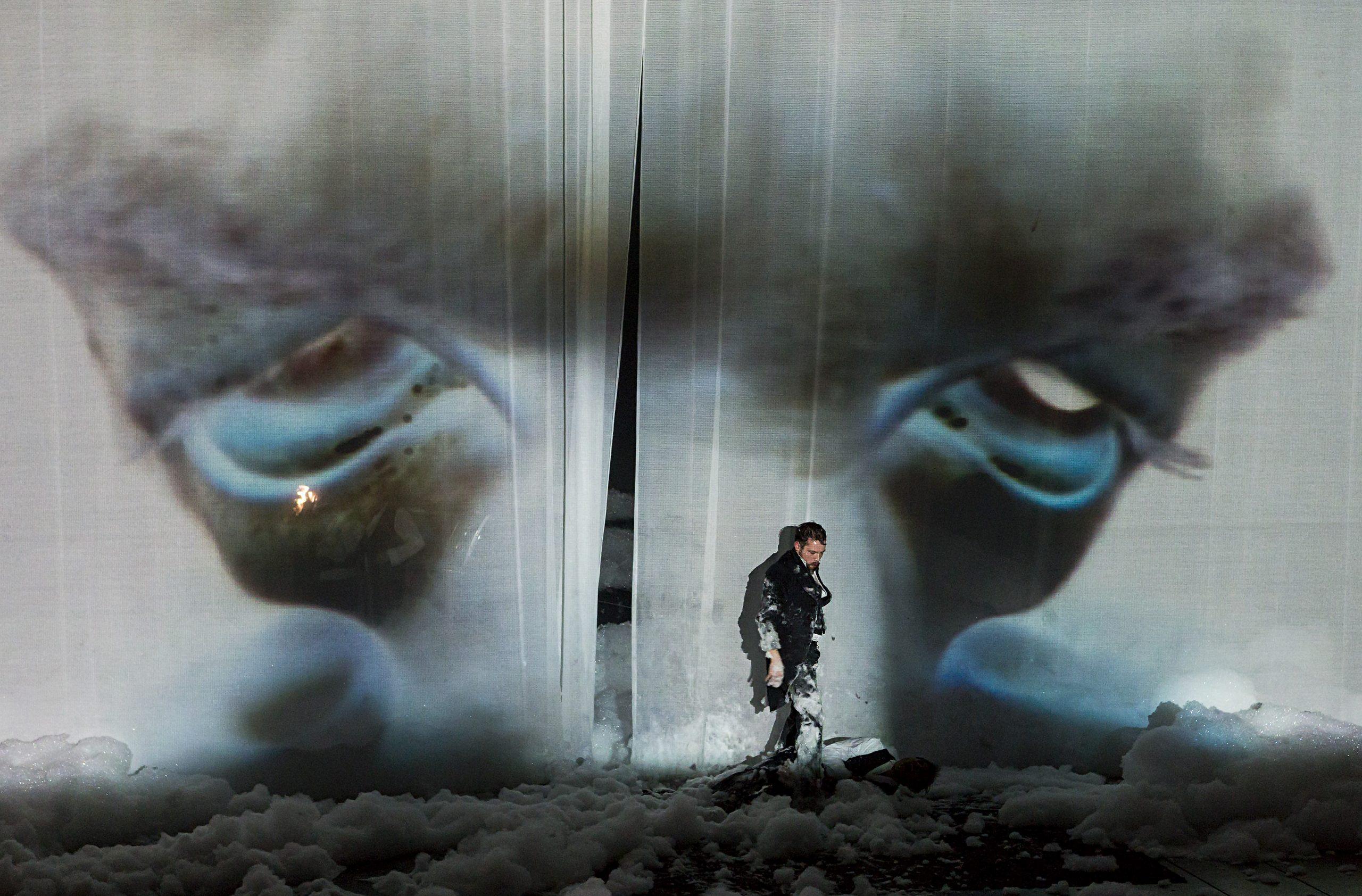 Foto: Rolf Arnold. Ein Mann in schwarzer Kleidung steht vor einem weißen semi-transparenten Vorhang, auf dem ein verzerrtes Negativ-Abbild eines vornübergebeugten Gesichts mit hoher breiter Stirn, heruntergezogenen blau unterlaufenen Augen und eingefallenen Wangen überdimensional groß zu sehen ist. An der Kleidung des Mannes befinden sich Reste des Schaumes, der über den ganzen Bühnenboden verteilt in unterschiedlichen Höhen liegt.