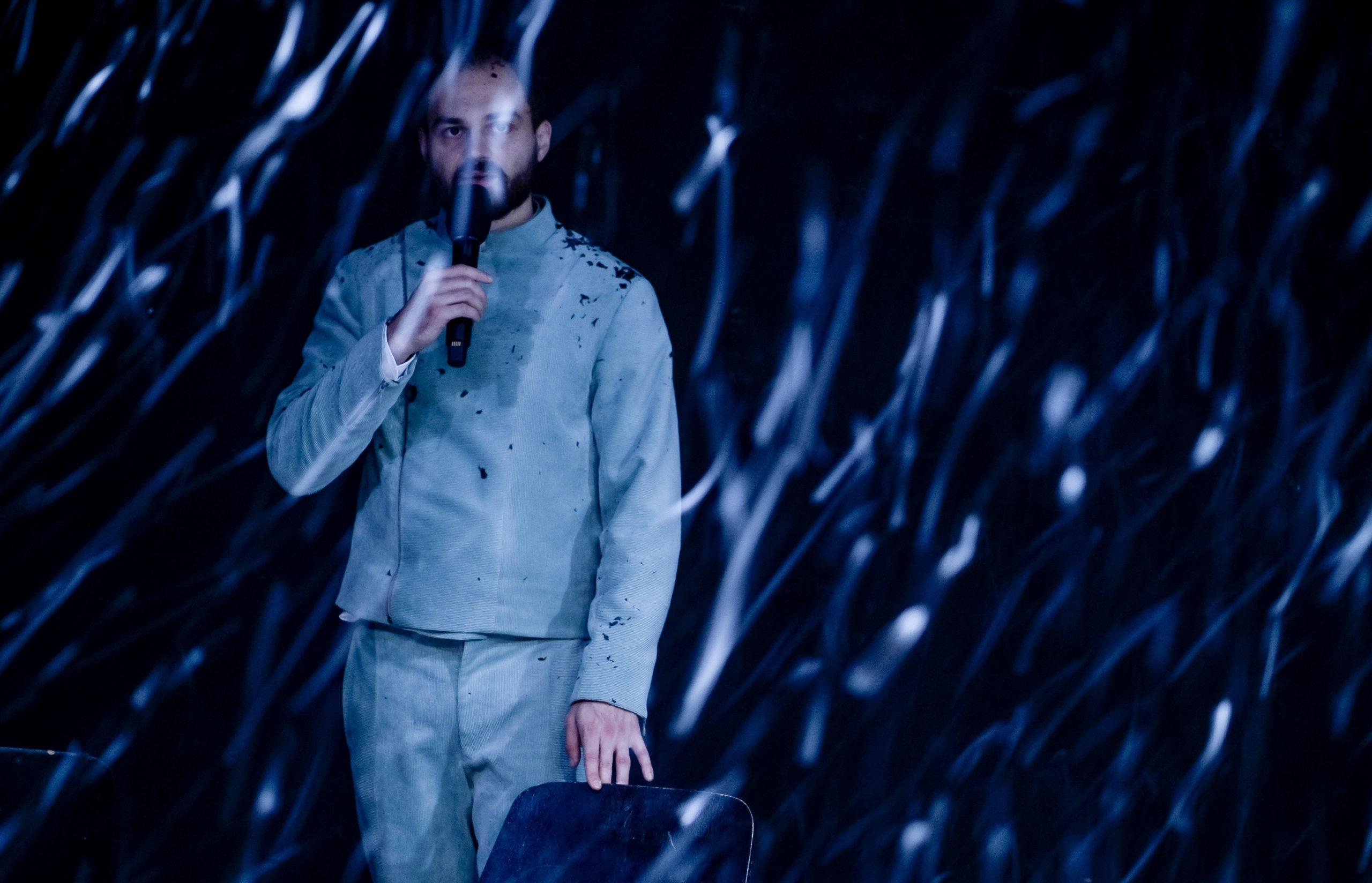 Die Pest © Arno Declair. Božidar Kocevski trägt einem hellblauen Anzug und steht auf einer dunklen Bühne mit Mikrofon vor dem Mund. Der Zeigefinger der anderen Hand berührt leicht den vor ihm stehenden Stuhl. Er ist umgeben von silbrig-hellblauen Fäden, die von der Bühne hinunterrieseln.
