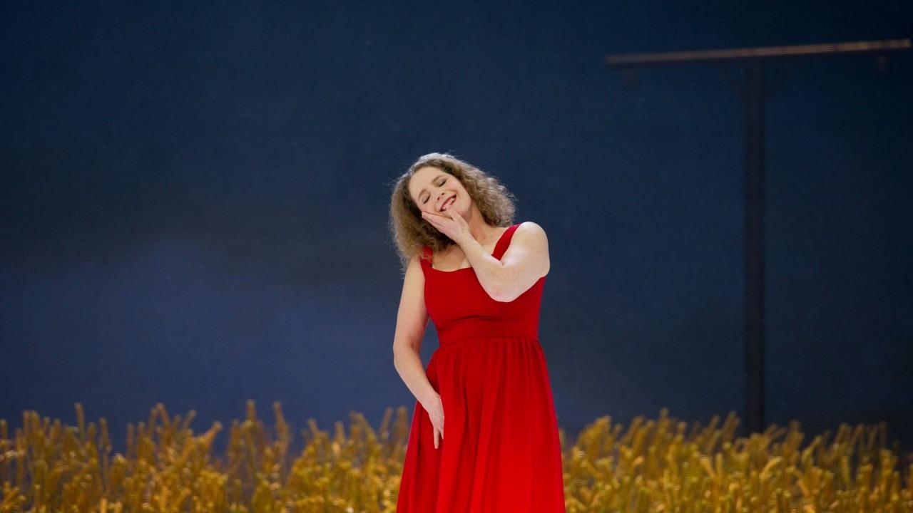 Jenufa © // Bettina Stöß. Eine Frau mit blonden schulterlangen welligen Haaren, steht in einem roten Kleid vor einem Ährenfeld unter dunkelblauem Himmel, hält ihre rechte Hand an den schräg gestellten Kopf und lächelt.