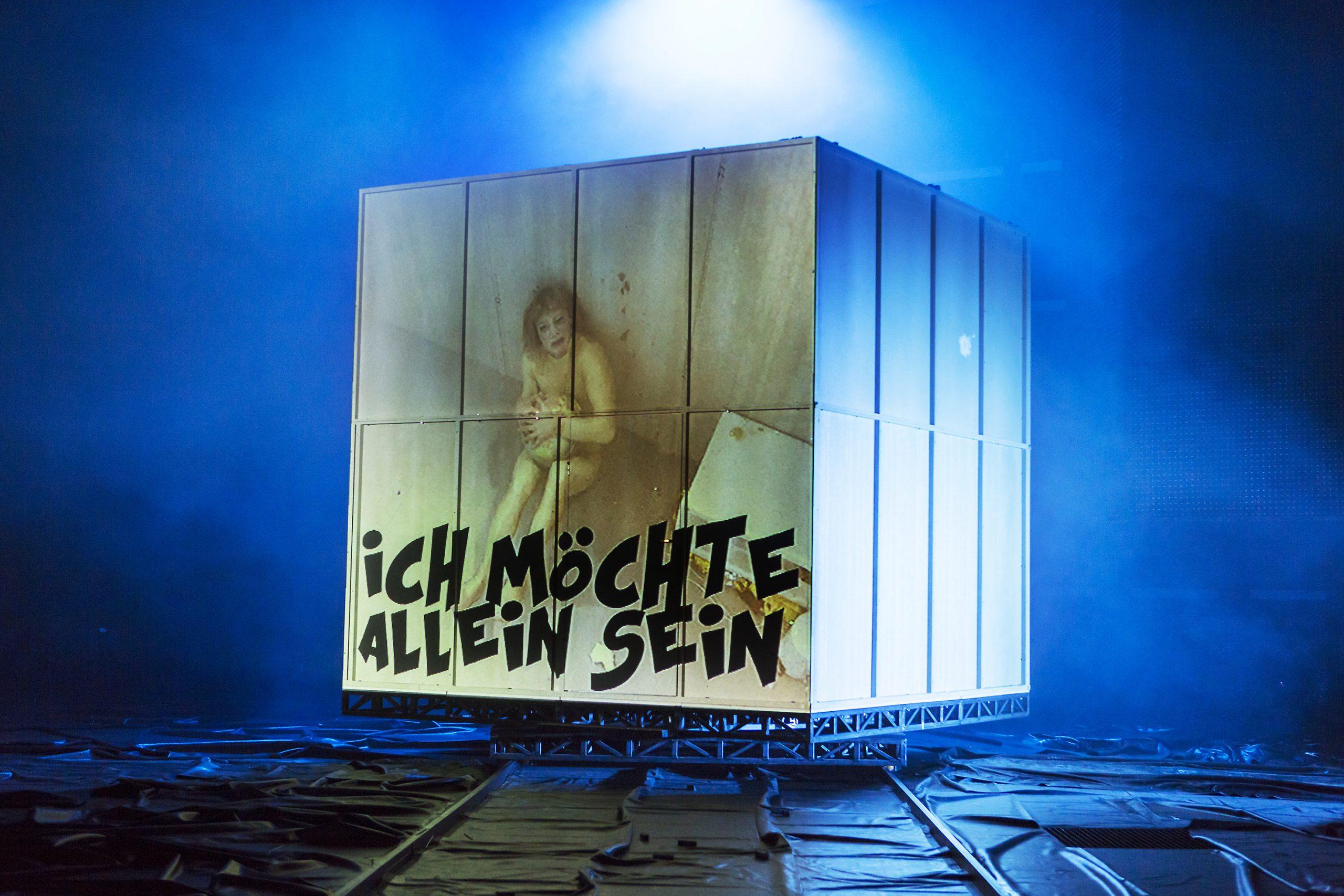 """© Rolf Arnold. Auf einer blau beleuchteten Bühne steht ein großer Würfel auf einer flachen Metallkonstruktion. Auf der vorderen Seite des Würfels ist eine Frau gemalt. Sie sitzt mit leicht angewinkelten Beinen auf dem Boden eines leeren Raums und hält einen Beutel vor ihrem Bauch. Sie schaut nach oben. Im unteren Bereich ist zu lesen: """"Ich möchte allein sein""""."""