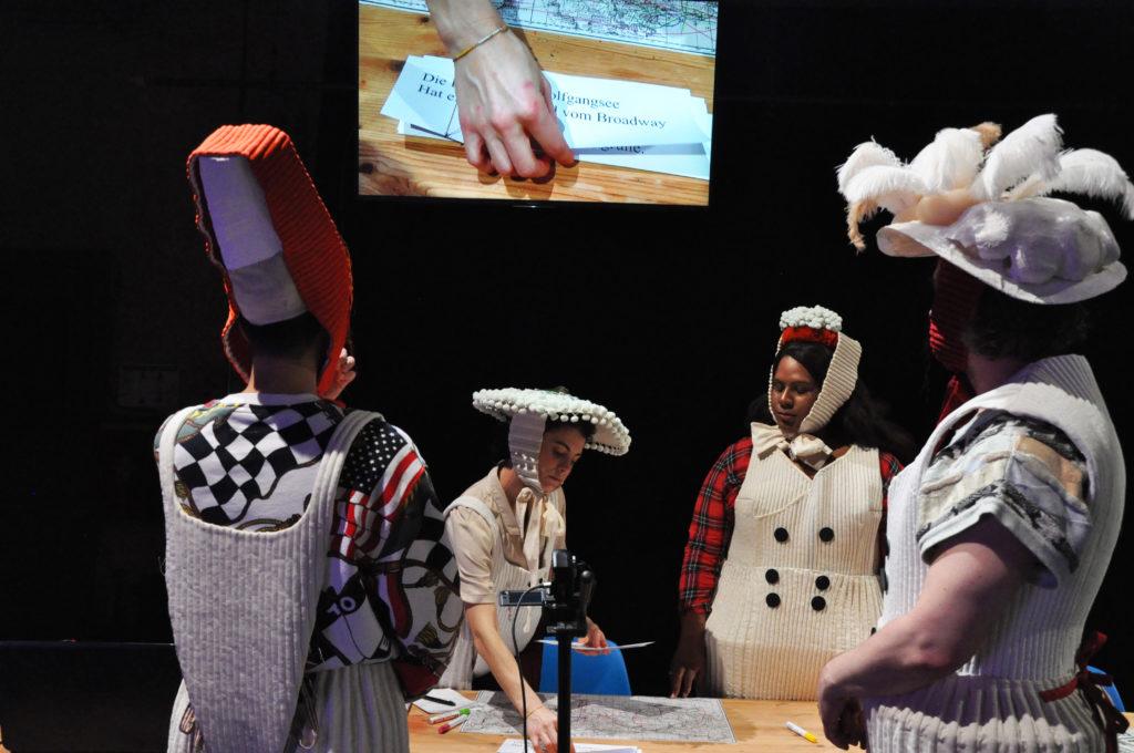 © Philine Rinnert. Vier Figuren in Kostümen stehen um einen Tisch. Hinter ihm werden die Bewegungen auf dem Tisch per Videocam auf eine Leinwand projiziert. Die Kostüme der Protagonisten bestehen aus fantasievoll gestalteten ausladenden Hüten und weißen oder grauen Strickkleidern.