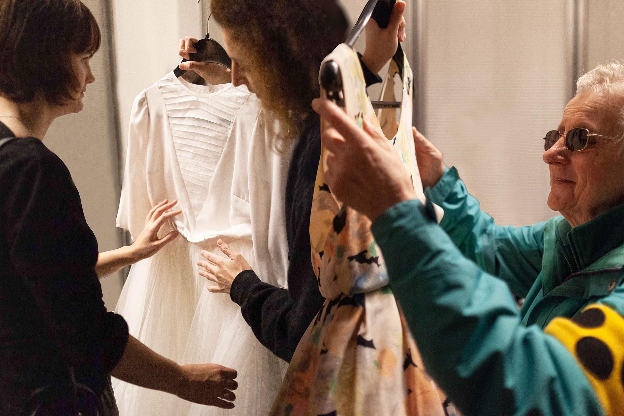 Berliner Ensemble Tastführung. Fotocollage: Christiane Reinsch. Lavinia ist links zu sehen. Sie hat ein schwarzes Oberteil an und fühlt ein weißes Kleid, das ihr von einer Mitarbeiterin auf einem Bügel gehalten wird. Roswitha, auf der rechten Seite, befühlt ein gemustertes Sommerkleid. Sie trägt eine türkisblaue Jacke und hat eine Blindenbinde um ihren Arm.