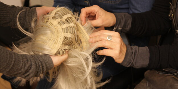 Othello, Berliner Ensemble. © Inga Dreyer. Eine Perücke mit hellblondem Haar wird von einer Person in einem grauen Pullover zur Unterseite umgedreht, sodass das Gewebe zu sehen ist und die langen Strähnen nach unten fallen. Auf der rechten Seite sind die Hände und Arme einer anderen Person zu sehen, die die Perücke mit beiden Händen ertastet-