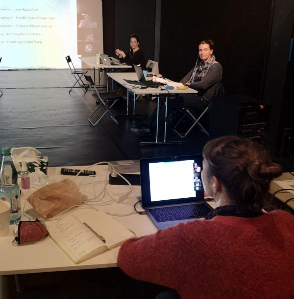 © Imke Baumann. Der Theaterraum mit schwarzen Wänden: Anke Nicolai sitzt mit dem Rücken zum Betrachter an einem Tisch. Vor ihr liegt ein Laptop, dessen Bildschirminhalt sich auf der großen Projektionsfläche abbildet. An der rechten Wand sitzen Jutta Polic und Eva-Katherina Jost an ihren Tischen und schauen zu Anke.
