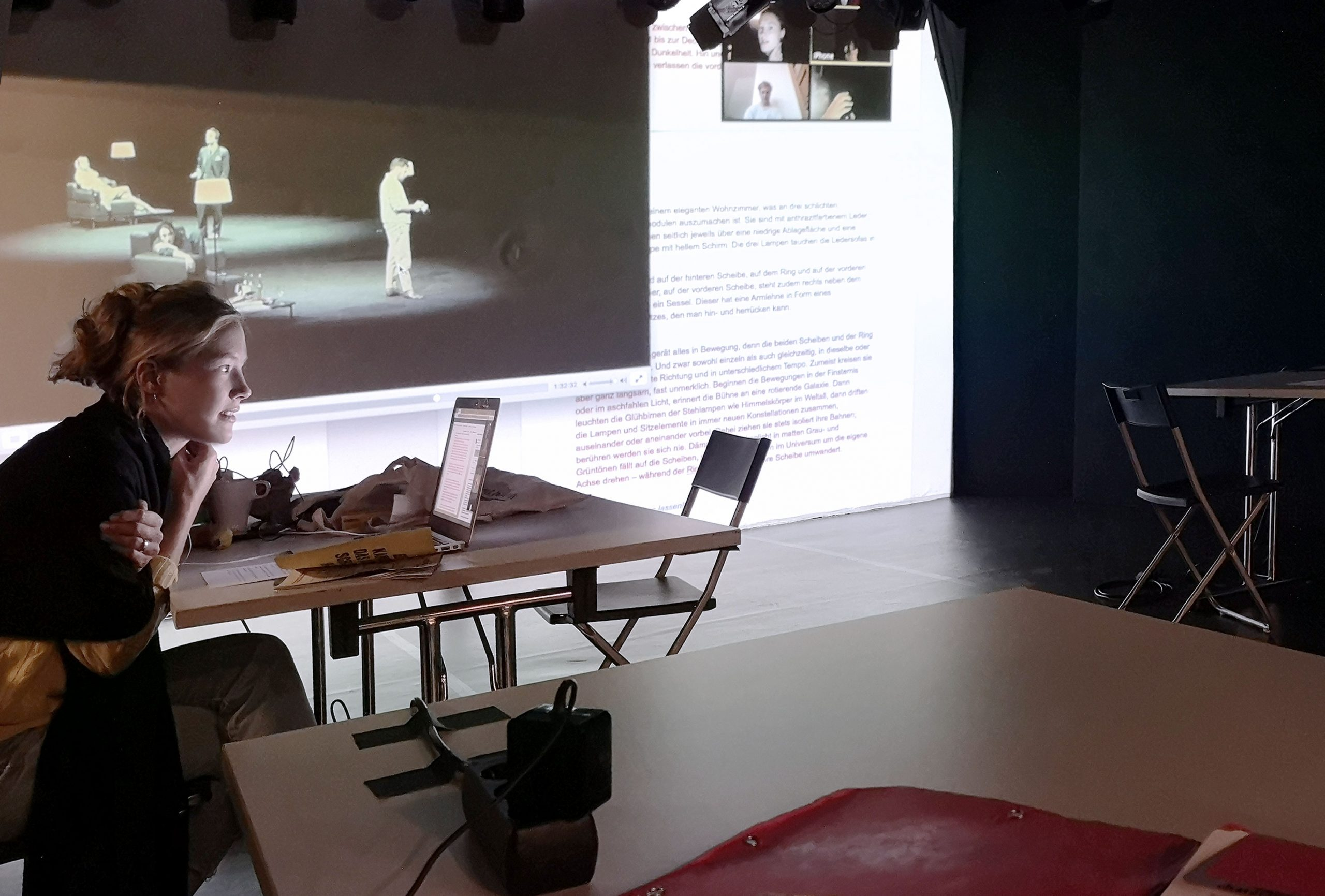 © Imke Baumann. Die Audiodeskriptorin Charlotte Miggel sitzt an einem Tisch, vor ihr liegt ein Laptop. Seitlich von ihr ist eine große Projektionsfläche mit dem Video einer Spielszene zu sehen, dahinter ist eine weiße Fläche mit Text und im oberen abgetrennten Teil die vier Teilnehmer, die per ZOOM dazu geschaltet sind.