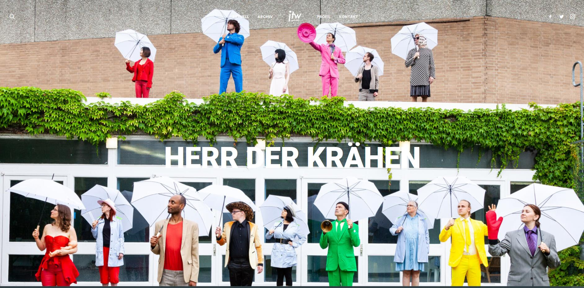 """© Foto und Grafik: Patryk Witt, www.jtw-spandau.de, Screenshot . Menschen in bunter Kleidung schauen alle in einer Richtung nach oben und halten aufgeklappte weiße Regenschirme in ihren Händen. Sie stehen vor einer Eingangsfront mit weißen Fensterrahmen und auf dem efeubewachsenen Vordach des Eingangs. Auf den waagerechten Fenstern der Eingangsfront steht in weißen Lettern """"HERR DER KRÄHEN""""."""
