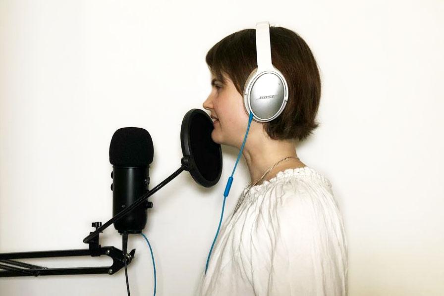 © Bjarke Walling. Lavinia Knop-Walling steht im Profil mit einem weißen Kopfhörer und weißer Bluse vor zwei schwarzen Mikrofonen. Ganz nah an ihrem Mund befindet sich ein tellerförmiges Mikrofon, das andere hat eine längliche Form. Beide sind an einem waagerechten Ständer befestigt..