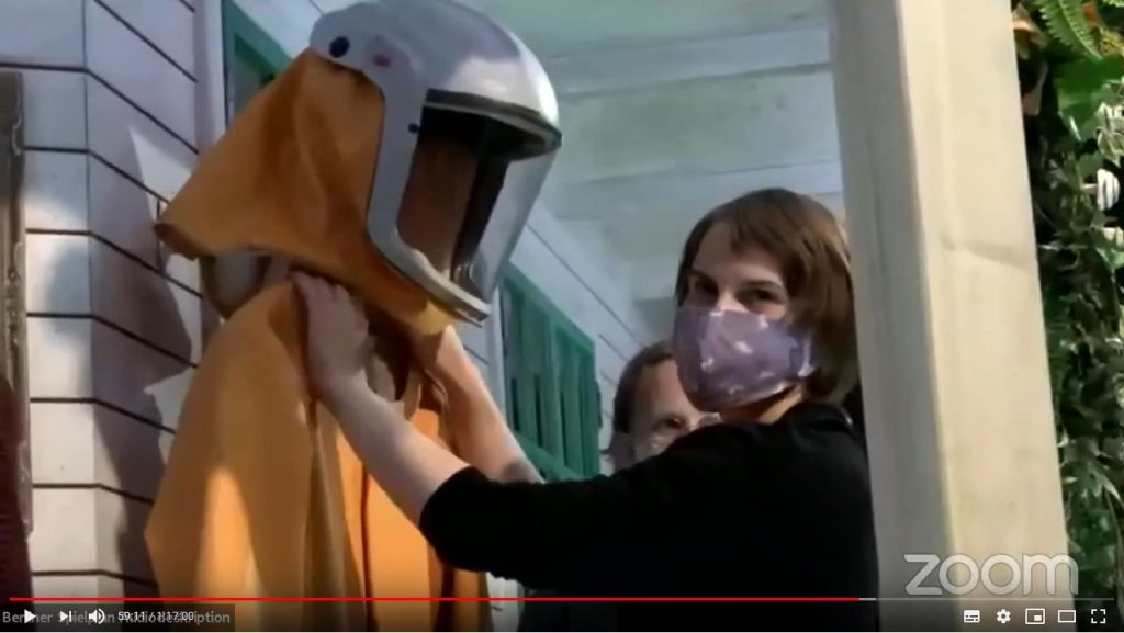 ZOOM Screenshot: Lavinia fühlt den orangenen Schutzanzug an der Halsgegend und schaut in die Kamera. Sie steht auf der Veranda und der Anzug mit dem weißen Helm hängt an der Veranda-Wand.