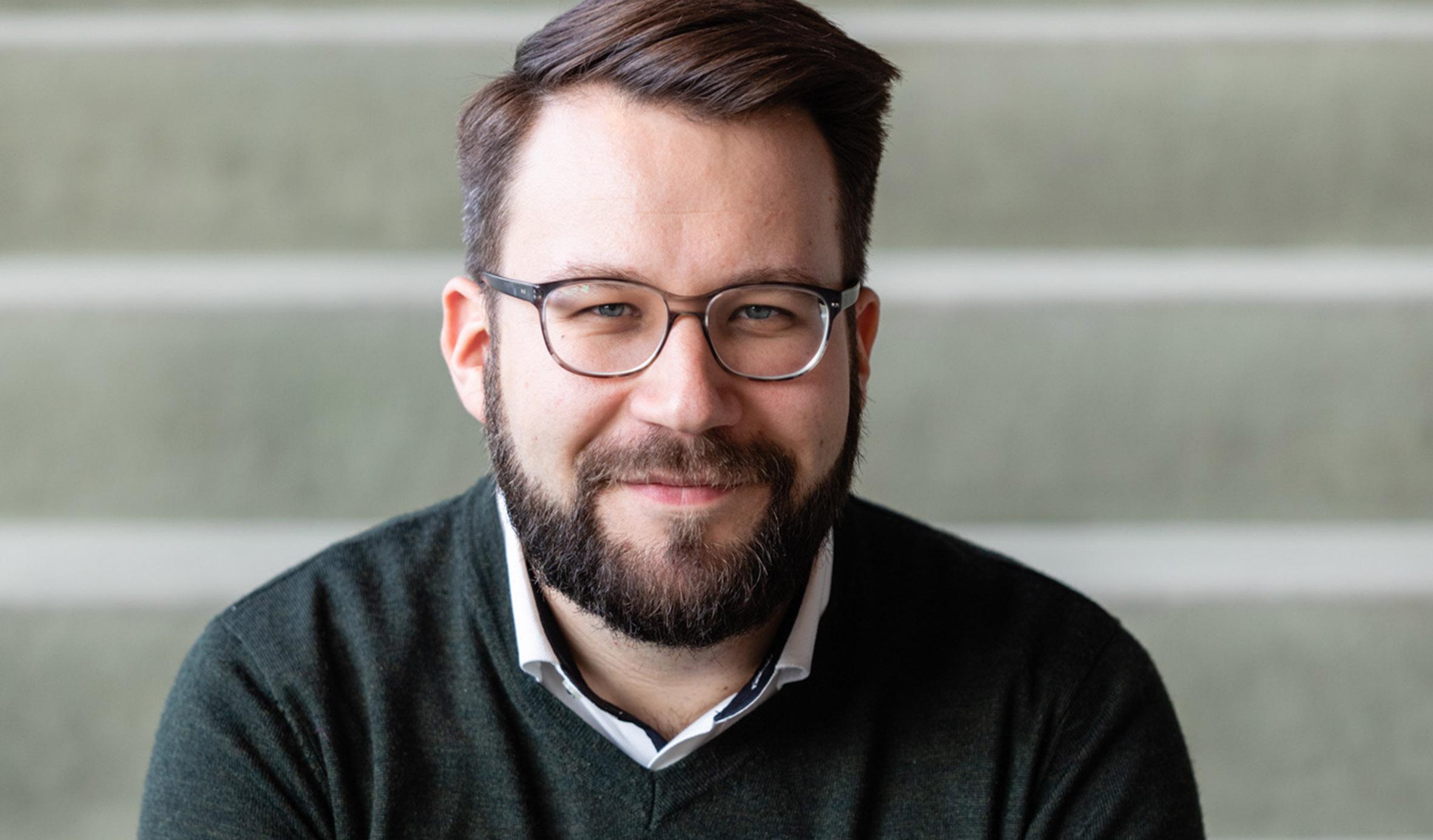 © Stephan Bögl. Porträt von Lars Gebhardt, Dramaturg, Deutsche Oper Berlin vor einem hellen Hintergrund mit weißen Streifen. Über einem weißen Hemd hat er einen anthrazitfarbenen Pullover mit V-Ausschnitt angezogen. Er hat braune Haare, einen kurzen Vollbart, trägt eine schwarz-umrandetet Brille und lächelt in die Kamera.