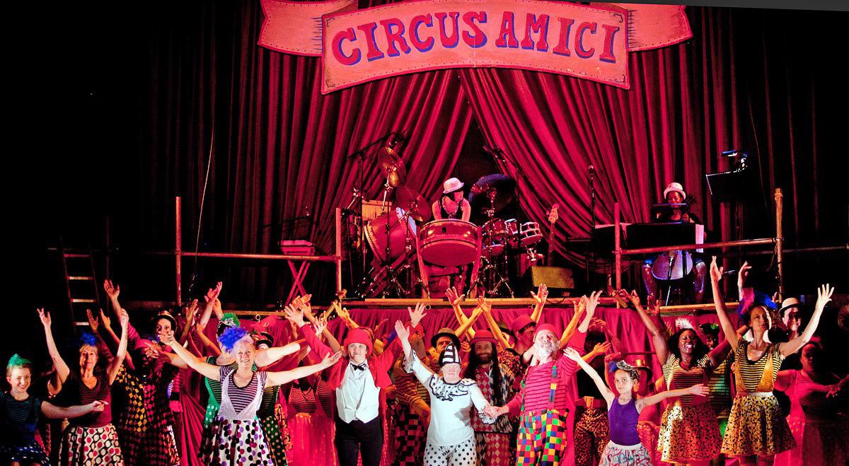"""© Nik Mackey. Amici Dance Theatre Company: Tightrope. Auf einer runden Bühne steht das Ensemble des Theaters in bunten Kostümen mit ausgebreiteten Armen. Hinter Ihnen ist ein Podest mit einem unteren roten Vorhang errichtet, auf dem mittig ein Schlagzeug aufgebaut ist und zwei Musikerinnen bei ihren Instrumenten sitzen. Der rote hintere Vorhang zieht sich durch den ganzen Bühnenraum, über dem das Schild """"Circus Amici"""" hängt."""
