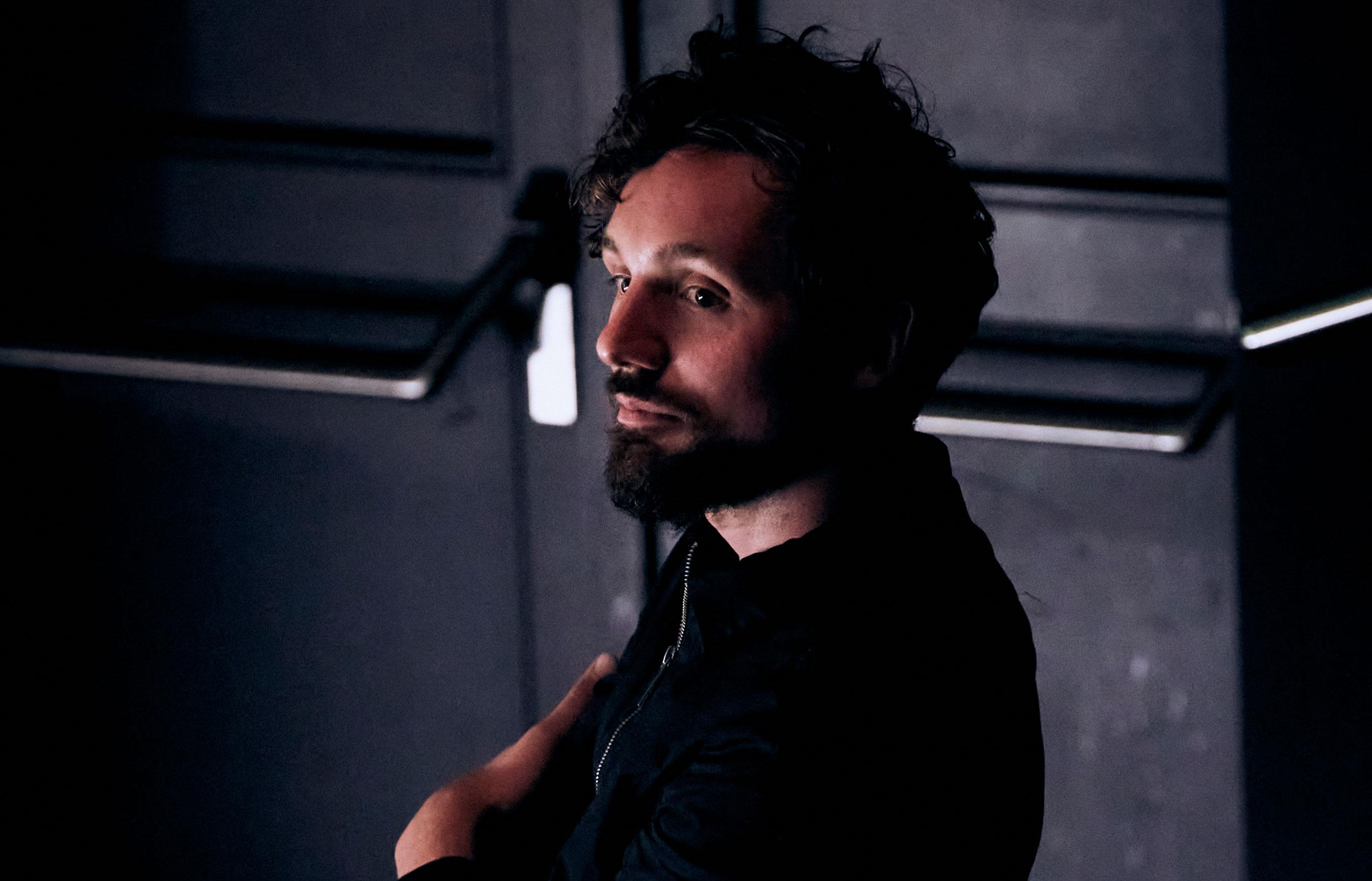 © Fabian Raabe. Justus Rothlaender ist vor einer schwarzen Tür mit Metallstangen aufgenommen, hat die Arme verschränkt und schaut im Halbprofil in den Raum. Er trägt ein schwarzes Hemd. Seine schwarzen kurzen lockigen Haare und der schwarze Bart korrespondieren mit dem dunklen Hintergrund.
