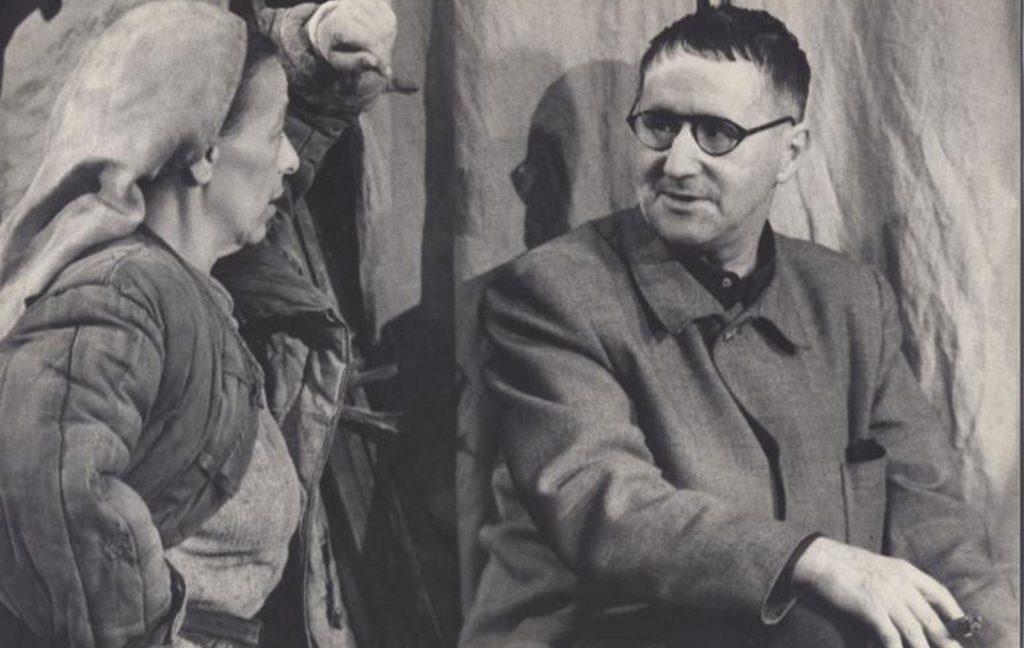 """© Hainer Hill © AdK, Berlin. Berliner Ensemble """"Mutter Courage und ihre Kinder"""", 1951. Helene Weigel lehnt sich mit einem hocherhobenen Arm an die Kulisse und schaut mit der anderen Hand an der Hüfte zu Bertolt Brecht. Dieser schaut sie von der Seite an. Er hat kurze dunkle Haare, eine schwarz-umrandetet Brille, trägt ein weites Arbeiter-Sakko und hält eine Zigarre in seiner rechten Hand."""