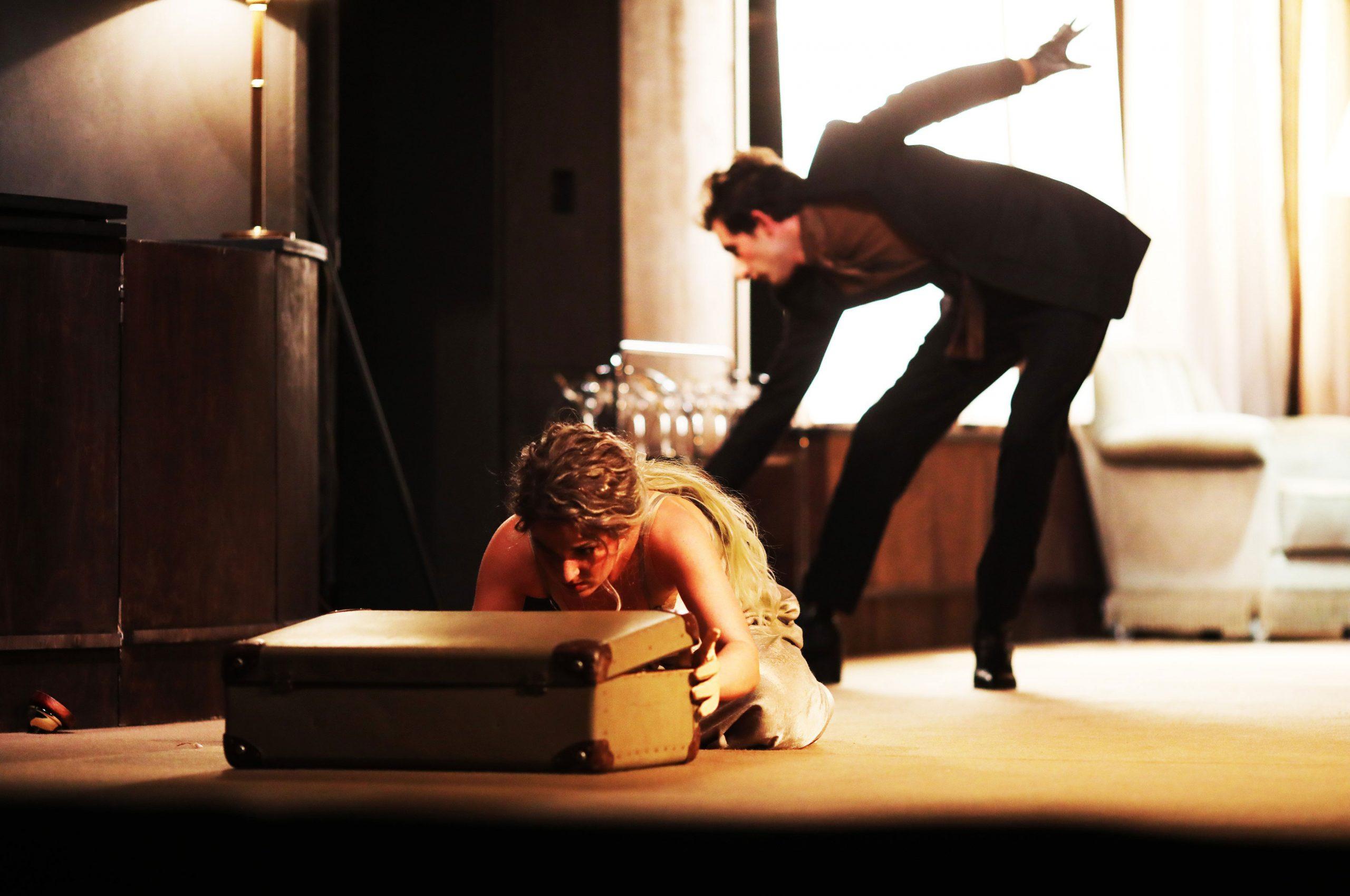 © Christian Brachwitz. Pythonparfum und Pralinen aus Pirgendwo. In einem in Brauntönen gehaltenen Hotelzimmer kniet eine Frau im Nachthemd vor einem auf dem liegenden alten etwas geöffneten Koffer. Ihre langen blonden welligen Haare sind nach hinten gebunden. Hinter ihr bückt sich ein schwarz gekleideter Mann in einer tänzerischen Körperhaltung Richtung Fußboden.