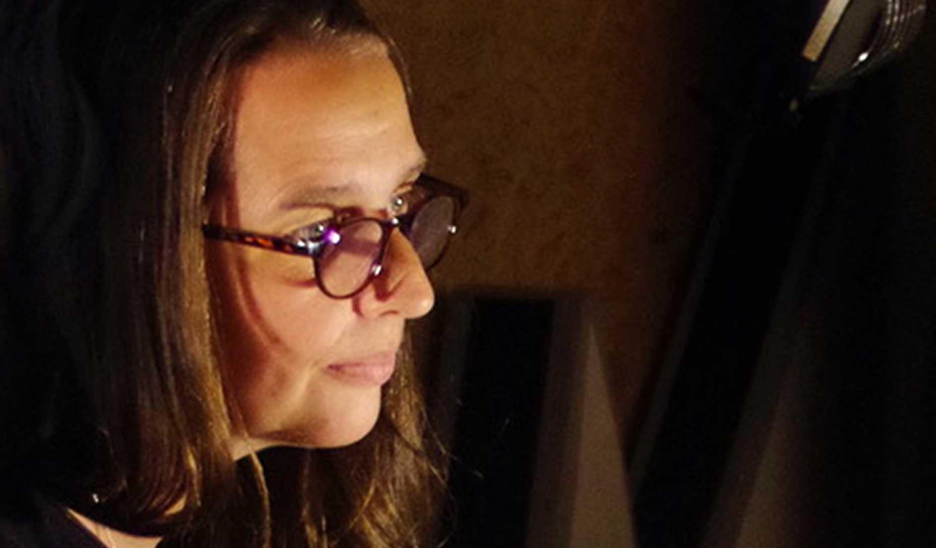 Jutta Polić ist im Halbprofil im Tonstudio von Dietrich Petzold zu sehen. Ein kleiner Baustrahler beleuchtet ihr Gesicht. Konzentriert blickt sie nach rechts, dort saß die Sprecherin, Nadja Schulz-Berlinghoff vor einem Bildschirm.
