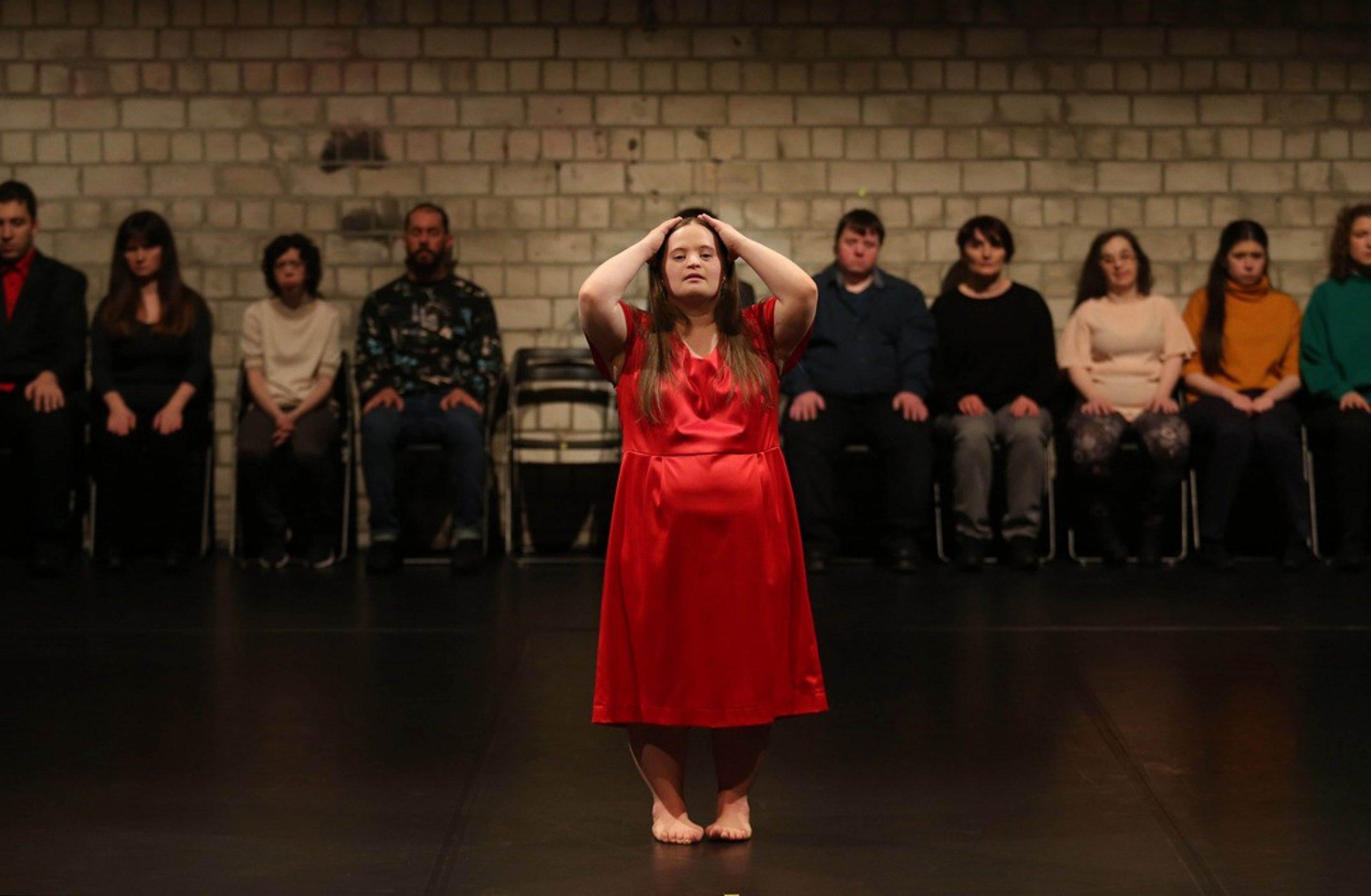 © Anja Beutler. Sophiensäle: Running Commentary on Dis_Sylphide. Eine Frau in einem roten Satinkleid steht mit geschlossenen Augen mittig im Bild und hat beide Arme auf ihren etwas erhobenen Kopf gelegt. Im Bildhintergrund an der weißen gemauerten Wand sitzt eine Reihe von Menschen in Alltagskleidung und schaut zum Publikum.
