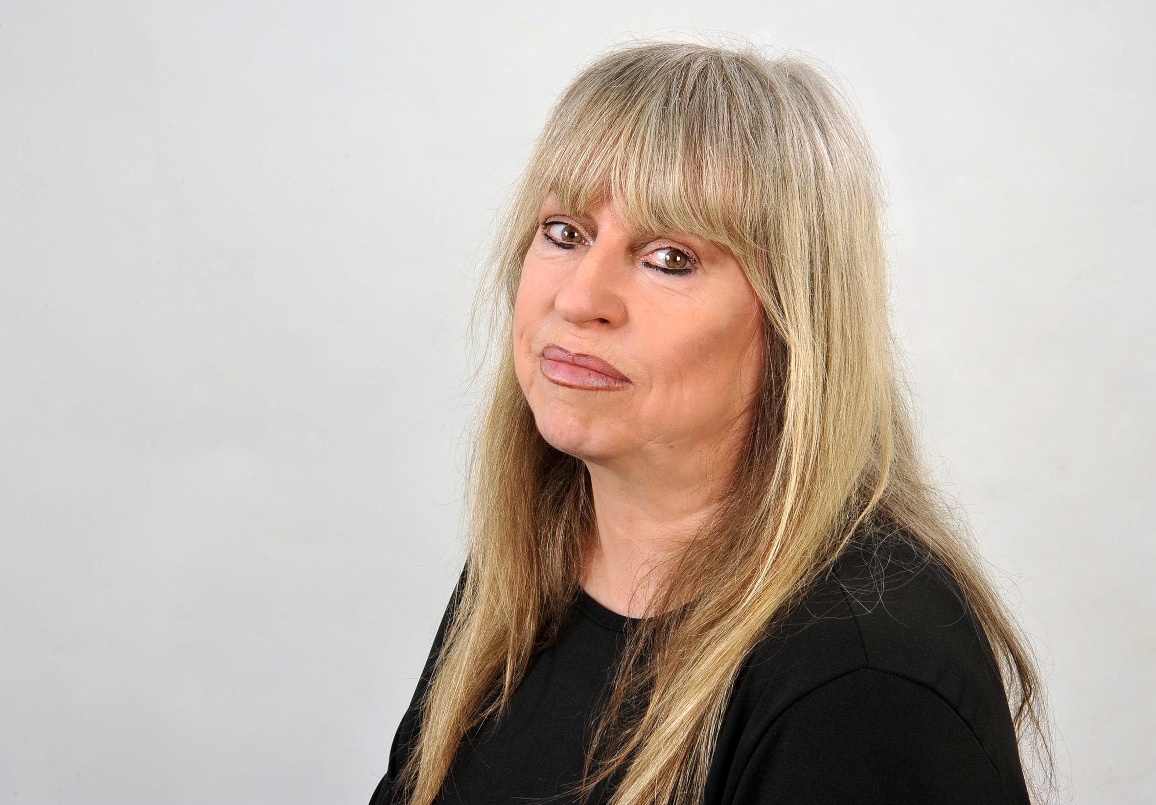 © Christina Kurby. Gina Pietsch hat ihren Kopf ein wenig nach hinten geneigt und schaut ernst in die Kamera. Sie hat lange blonde Haare, die weich auf den schwarzen Pullover herunterfallen mit einen Pony, und ihre Augen und ihr Mund sind geschminkt.