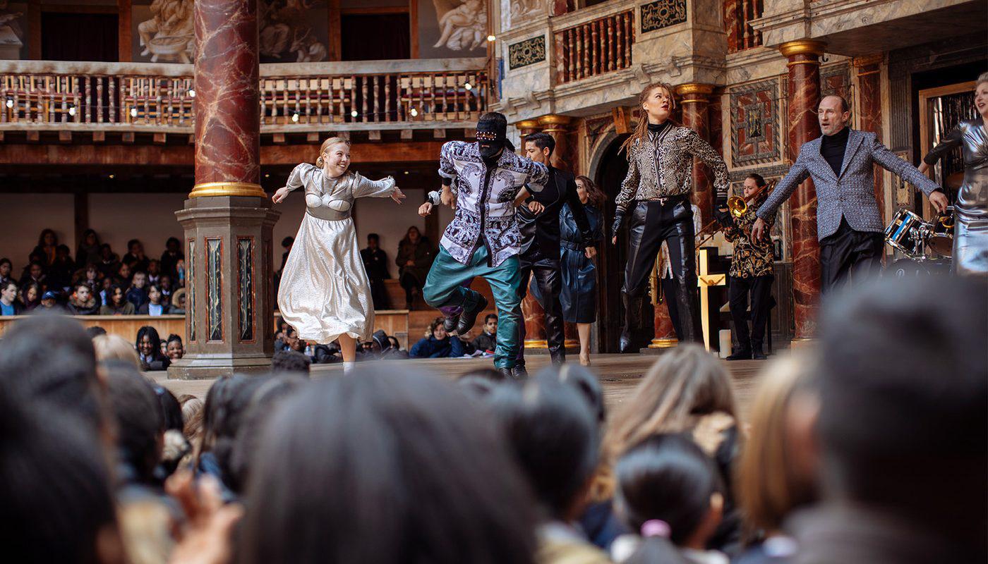 © Cesare De Giglio, Globe Theatre: Romeo and Juliet. Auf der Bühne des Globe-Theatres tanzen die Schauspieler teils in historischen, aber meist in zeitgenössischem Outfits einen modernen Tanz, indem sie nach vorne gebeugt die Arme weit ausbreiten und auf einem Bein hüpfen.