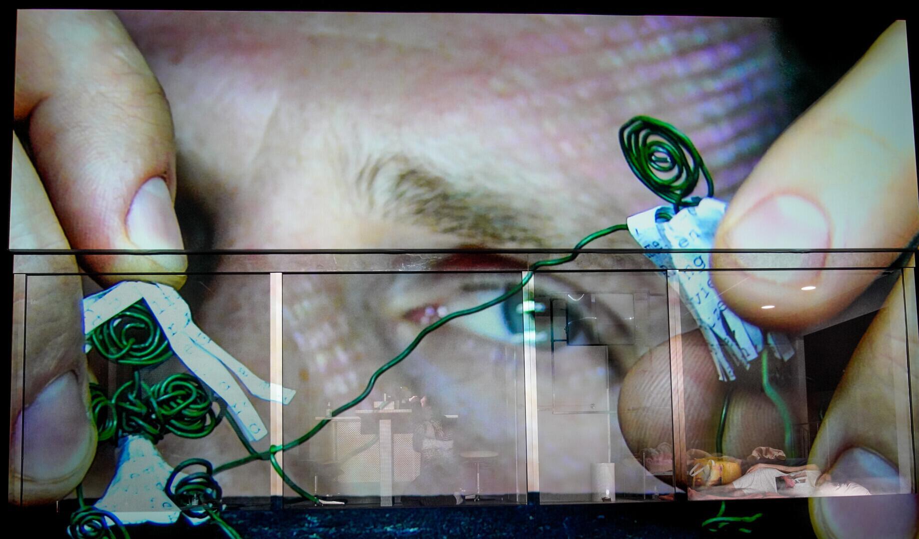 © Arno Declair, Woyzeck Interrupted. Die riesige Leinwandprojektion auf der Bühnenwand zeigt den Ausschnitt eines männlichen Kopfes der mit seinen Fingern verzweigte grüne Drähte, umgeben von kleinen Papierfransen, anfasst und diese Konstruktion betrachtet.