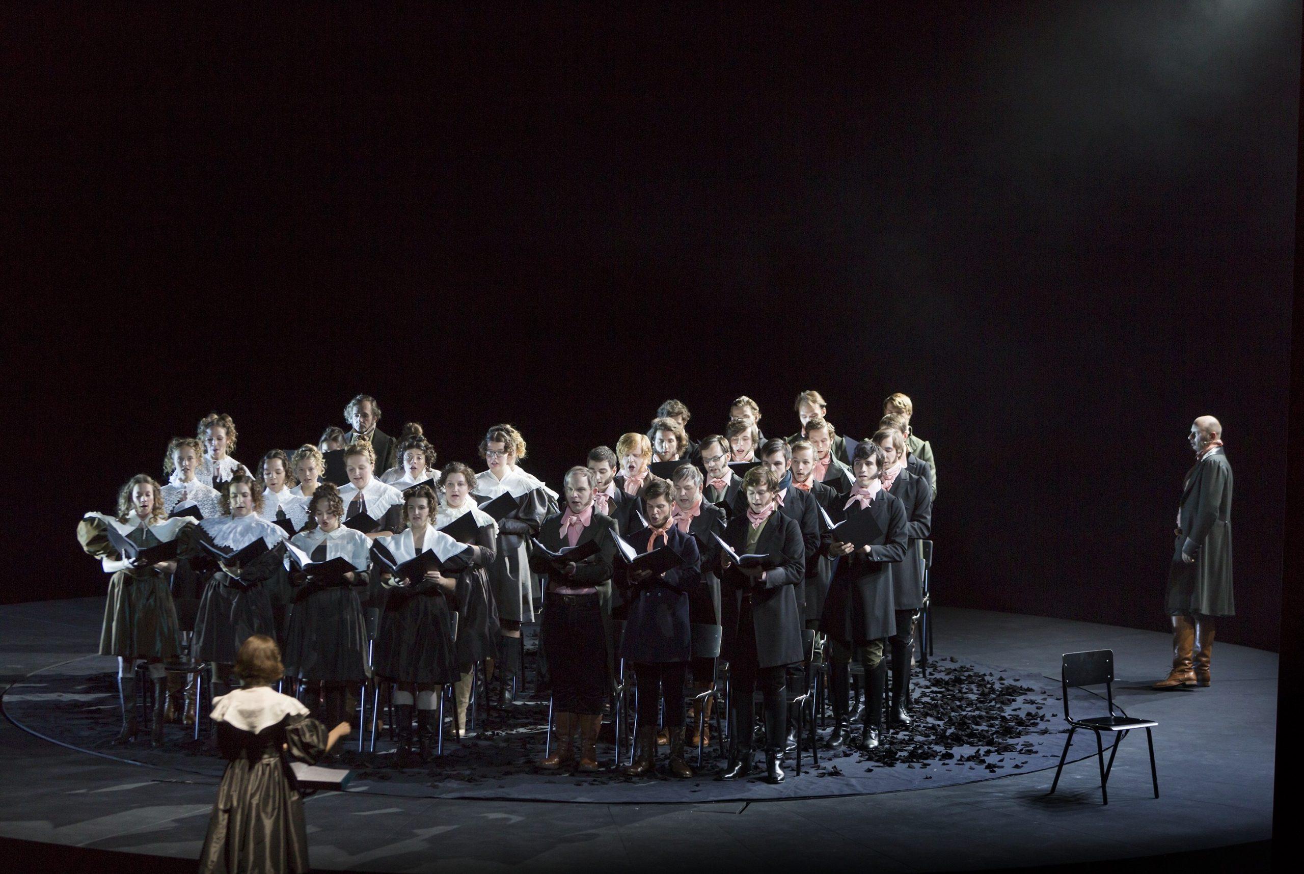 © Rolf Arnold, Faust. Auf einer schwarzen Bühne steht der Chor, der aus 19 Männern und 16 Frauen besteht, die in historischer dunkler Kleidung getrennt voneinander stehen und große schwarze aufgeklappte Bücher halten. Vor ihnen steht eine Frau und mit Abstand ein älterer Mann, der in die Ferne schaut