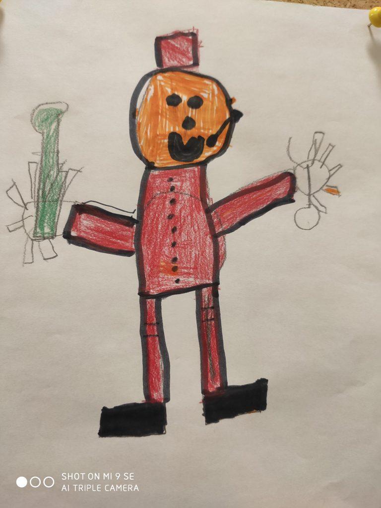 Ein Mann mit rundem orangefarbenem Gesicht und dicken Punkten für die Augen, einem dicken Punkt für die Nase und einem gebogenen Strich für den lächelnden Mund hat einen kleinen roten würfelförmigen Hut auf. Er trägt einen roten Anzug, dessen Oberteil mit kleinen Knöpfen geschlossen wird. Die Arme hält er waagerecht vom Körper, die Hände sind Kreise mit Stäbchen, die Finger andeuten. In der einen Hand hat er einen grünen Gegenstand.