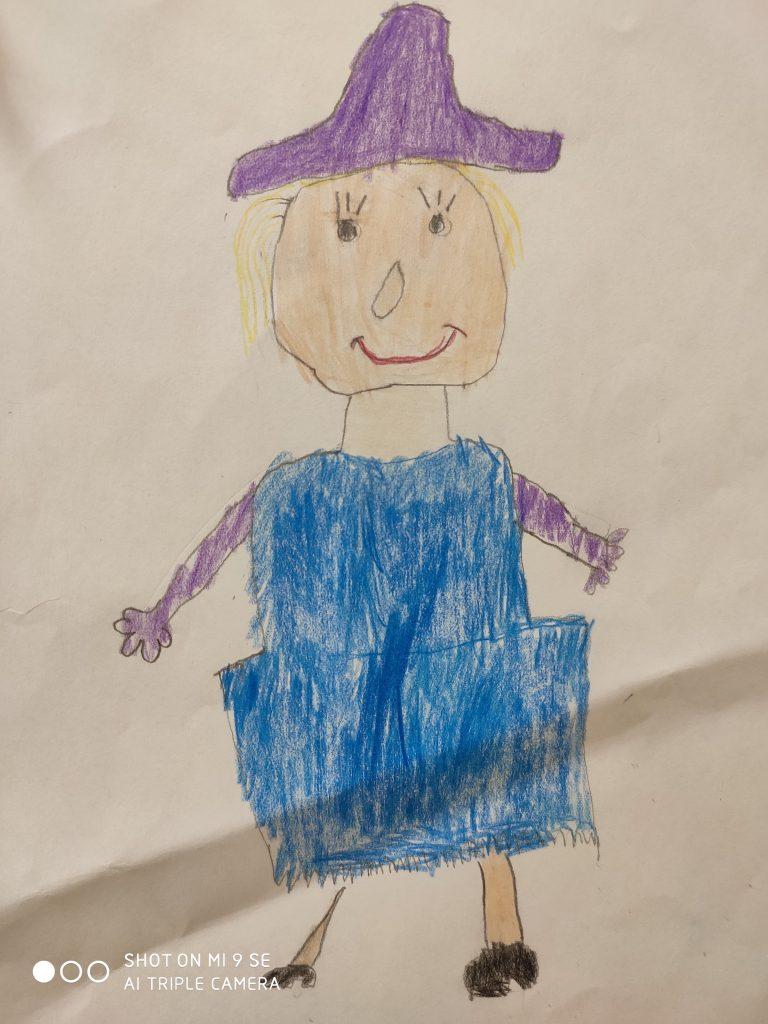 Eine Frau mit breitkrempigem lilafarbenem Hut, blonden Haaren und einem blauen Kleid.