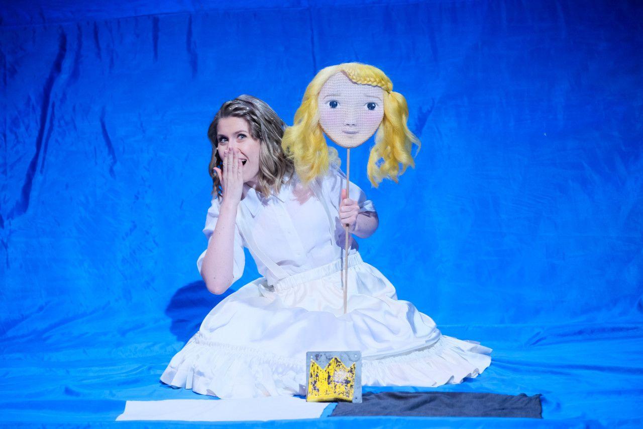 © Clemens Heidrich. Die Gänsemagd. Die Bühnenfigur sitzt in einem weißen Kleid auf dem Boden einer mit einem blauen Stoff ausgelegten Bühne. Sie hält ihre eine Hand vor ihrem offenen Mund und mit der anderen hält sie ein Schild an einem Stock, auf dem ein Mädchengesicht gemalt ist und an dem blonde lockige Haare an den Seiten baumeln.