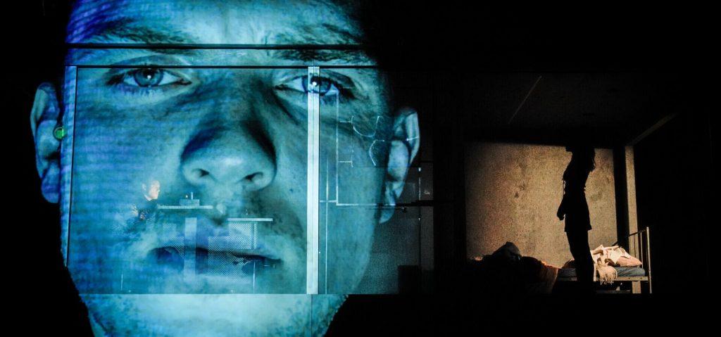 © Arno Declair, Woyzeck Interrupted. Die riesige Leinwandprojektion auf der Bühnenwand zeigt den  blau angestrahlten Kopf von Woyzeck. Daneben sind die Umrisse einer Frauenfigur auf der Bühne zu sehen.