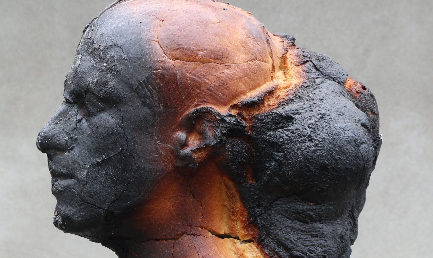 Hamlet – Teodora Castellucci / Dewey Dell. Photo & sculpture: © Matteo Lucca. Das gebackene Brot in Form einer männlichen Skulptur ist in Seitenansicht aufgenommen, wobei das verbrannt-schwarze Gesichtsprofil genau zu erkennen ist. Dahinter wölbt sich eine schwarze Masse aus dem Hinterkopf
