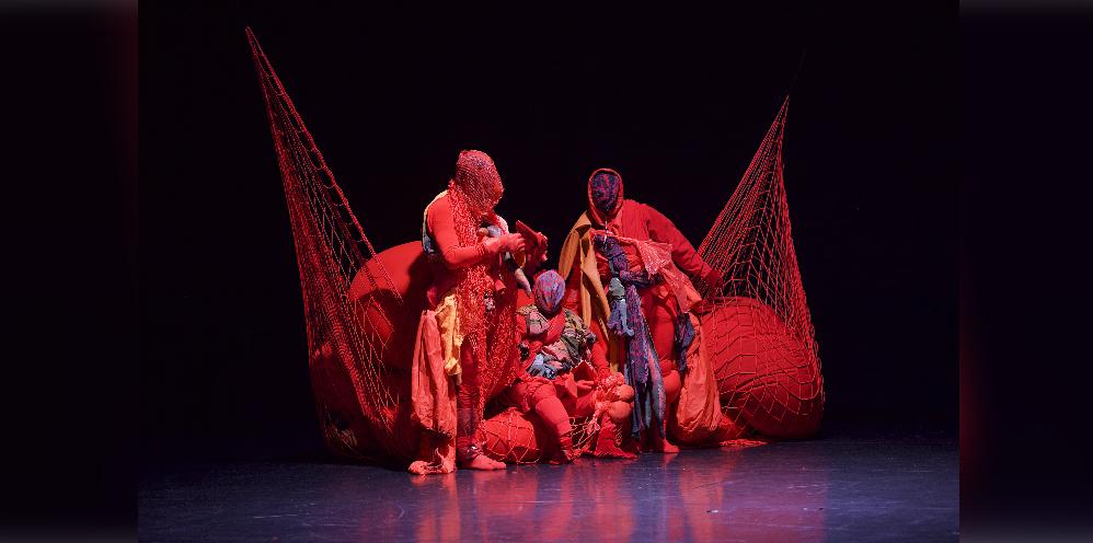 """Copyright: Dieter Hartwig. """"Alle Augen Staunen"""", Choreografie Lea Moro. Drei Personen mit zugebundenen Köpfen in bunten Outfits sind rot angeleuchtet. Hinter ihnen hängt ein rotes Netz, das an zwei Enden an der Decke befestigt ist."""