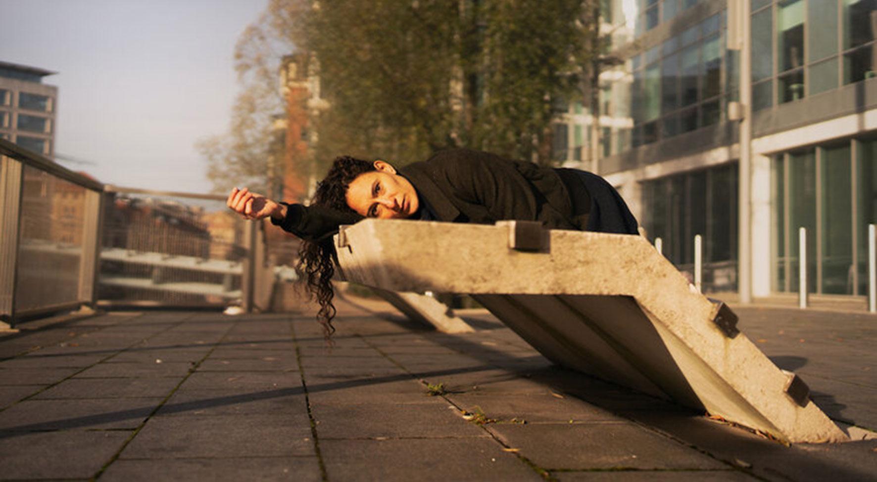 © Paul Samuel White. In einer betonierten Stadtlandschaft liegt eine Frau mit langen dunklen Haaren und einem schwarzen Outfit auf einem Betonelement und schaut in die Kamera.