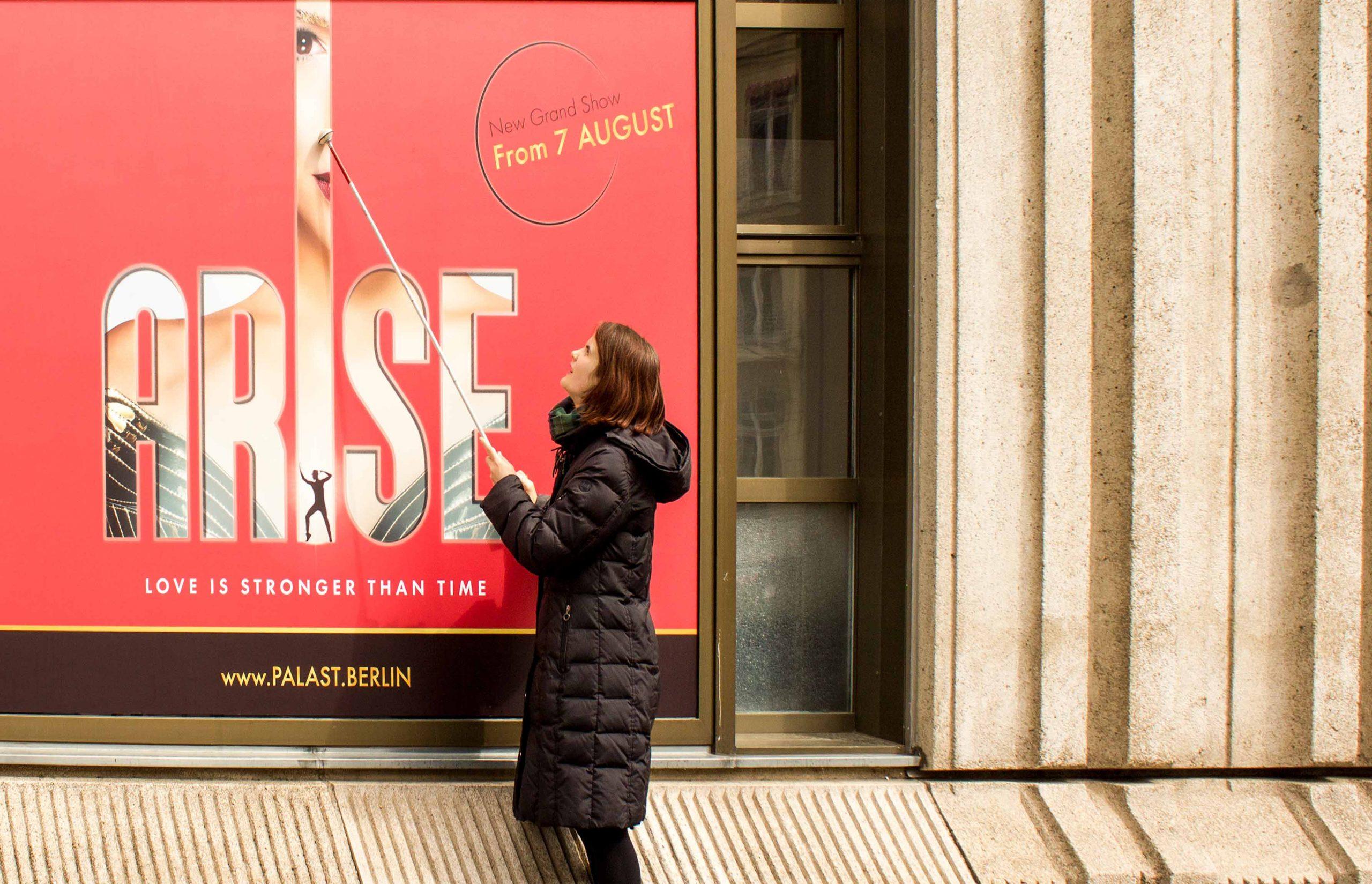 """© Christiane Reinsch: Lavinia steht vor dem Plakat am Friedrichstadt-Palast Berlin und zeigt mit ihrem Langstock auf den oberen Teil der Schrift des neuen Stücks """"Arise"""", die auf einem roten Hintergrund gesetzt ist."""