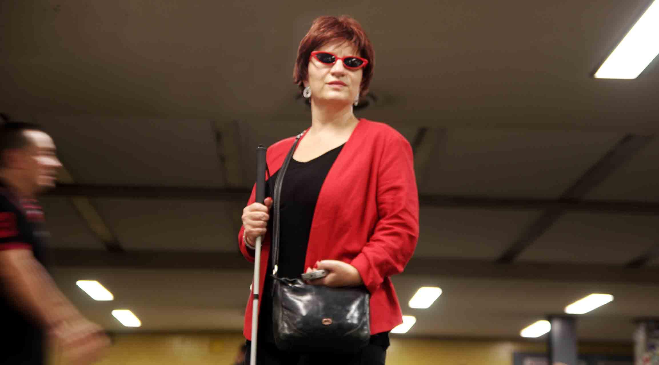 © Silja Korn. Silja Korn steht an einem Bahnsteig der U-Bahn. Sie trägt einen roten Blazer, eine rote Sonnenbrille und hält ihren Langstock in der einen, ein Smartphone in der anderen Hand.