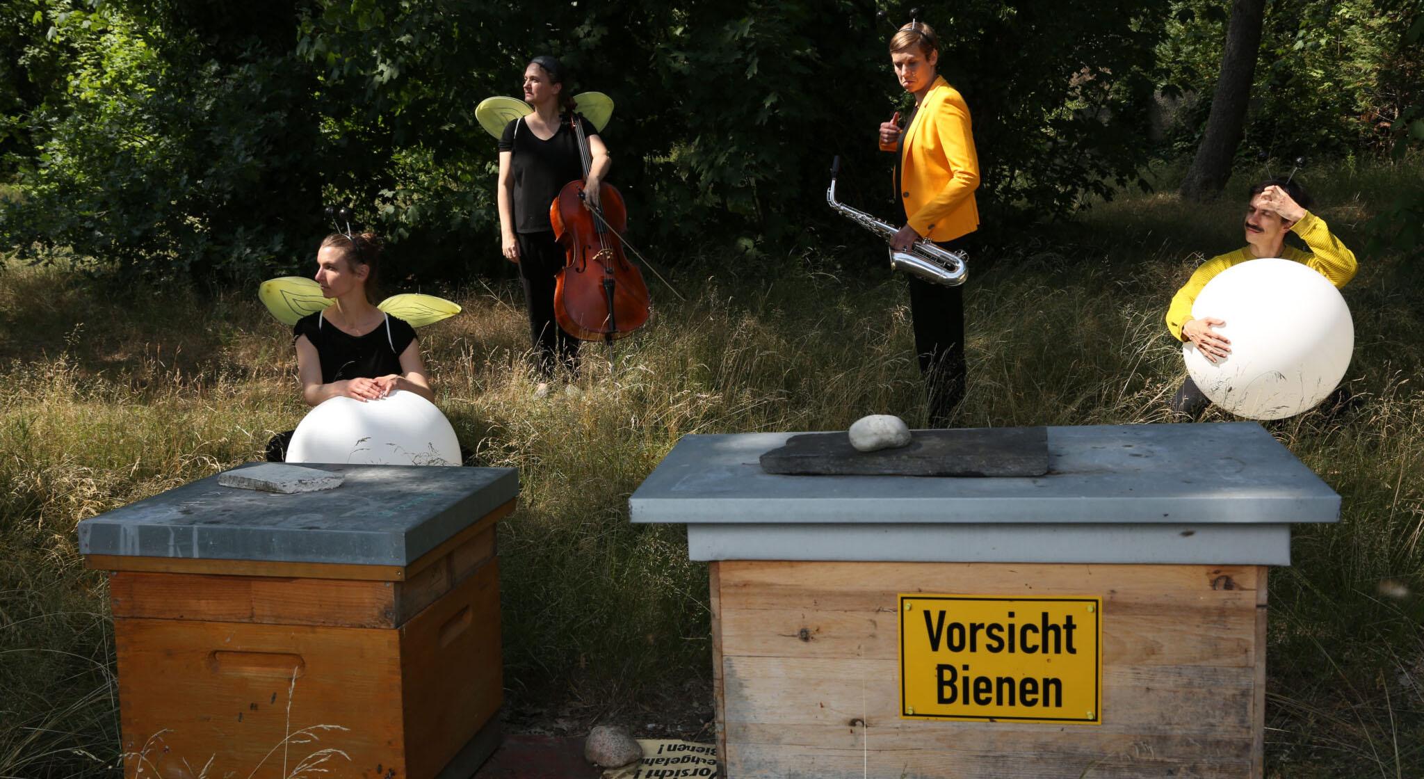 © Adam Berry: Die Ordnung der Dinge: Zum Beispiel Bienen. Zwei Performer*innen mit Flügelkostümen und weißen Ballons vor sich sowie zwei Musiker*innen mit ihren Instrumenten stehen hinter zwei Holzkästen. Auf einem Kasten ist ein Schild befestigt: Vorsicht Bienen.